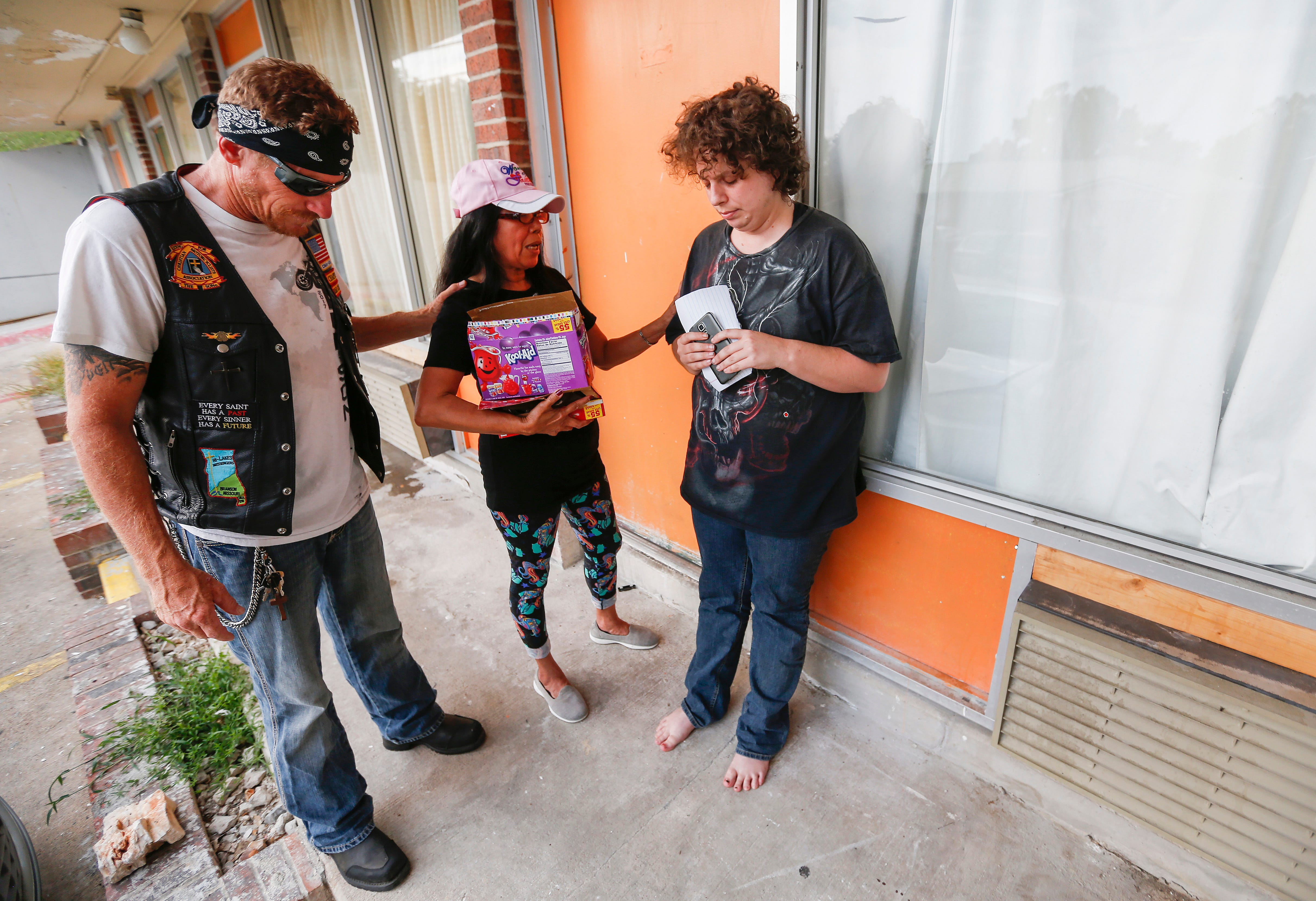 Rick Diamond and Estrella Wilson, volunteers with Jesus Was Homeless, pray with Ally Brown, right, after delivering meals for her family at the Branson Plaza on Thursday, July 5, 2018. Jesus Was Homeless volunteers deliver meals to residents in Branson's extended stay hotels every Thursday.
