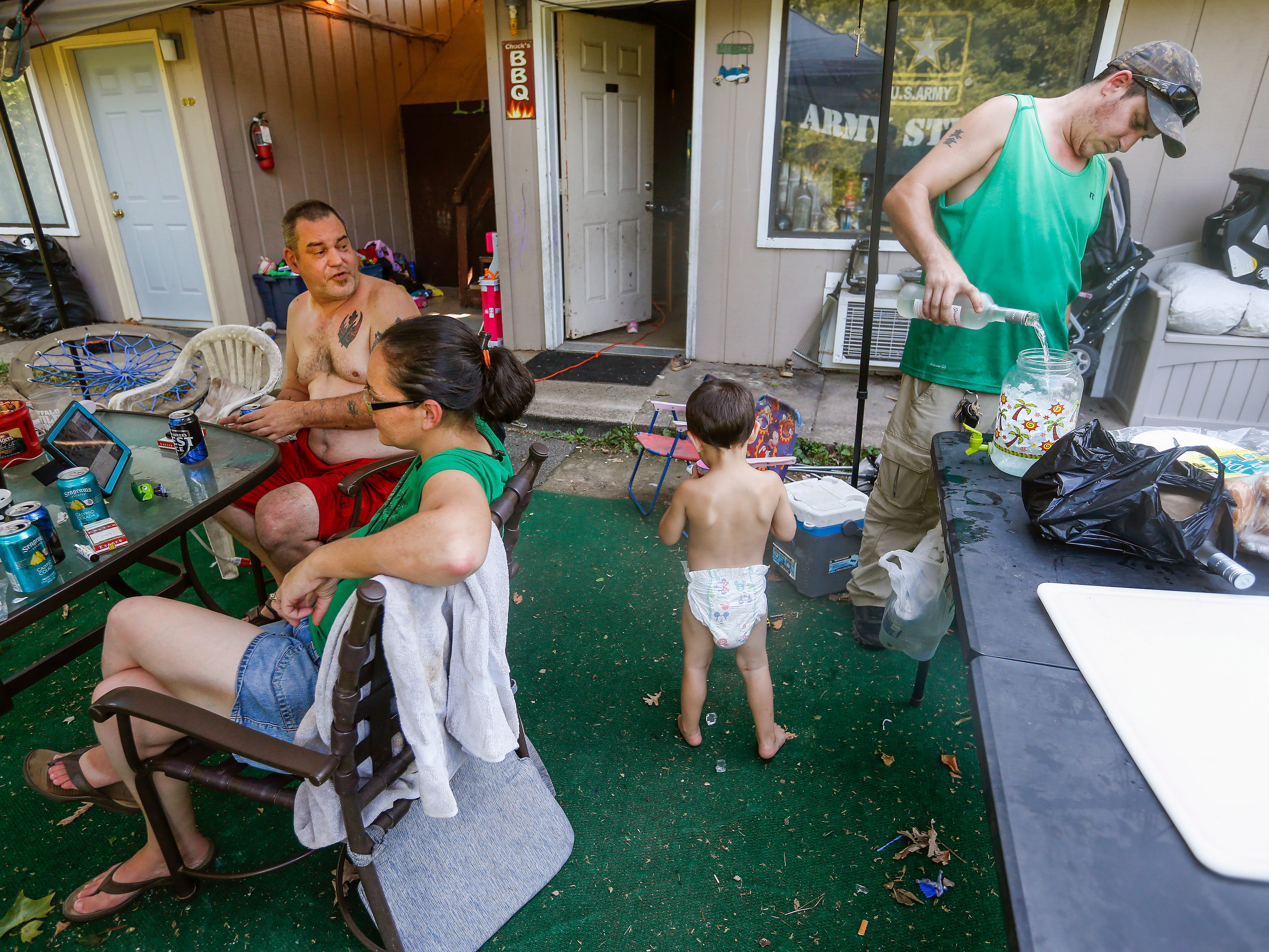 Chuck Stuedl and Amanda Norris along with their son Gabriel Norris, 3, relax as Jason Berriault mixes drinks while barbecuing and celebrating Amanda's birthday outside the extended stay hotel they live in in Branson on Friday, July 20, 2018. They spend most of their time outside their room in the outdoor seating area they created talking with friends and barbecuing.