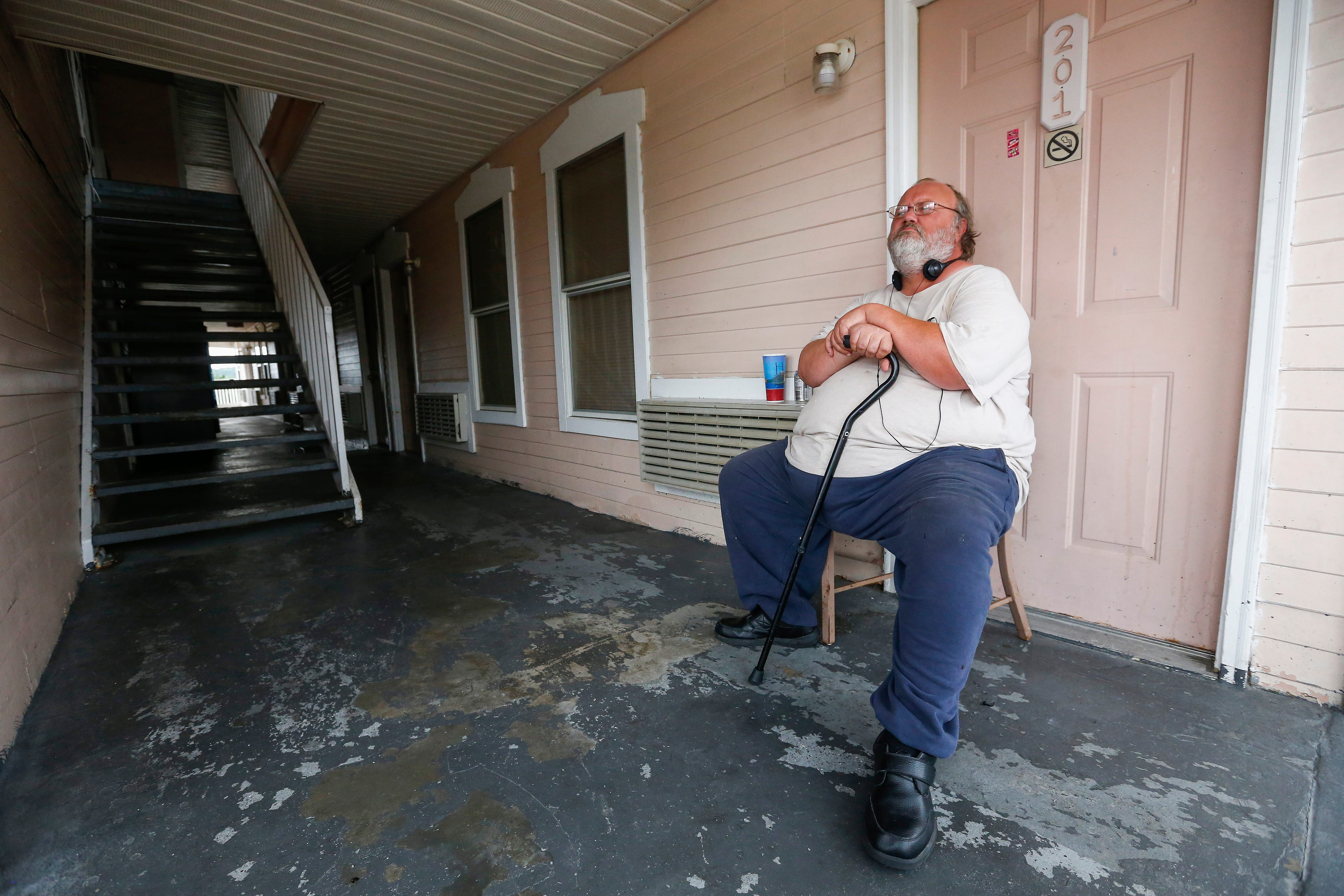 Rev. David Ellis sits outside his room at the Queen Anne Motel and watches the world go by on the Branson Strip on Wednesday, July 18, 2018.