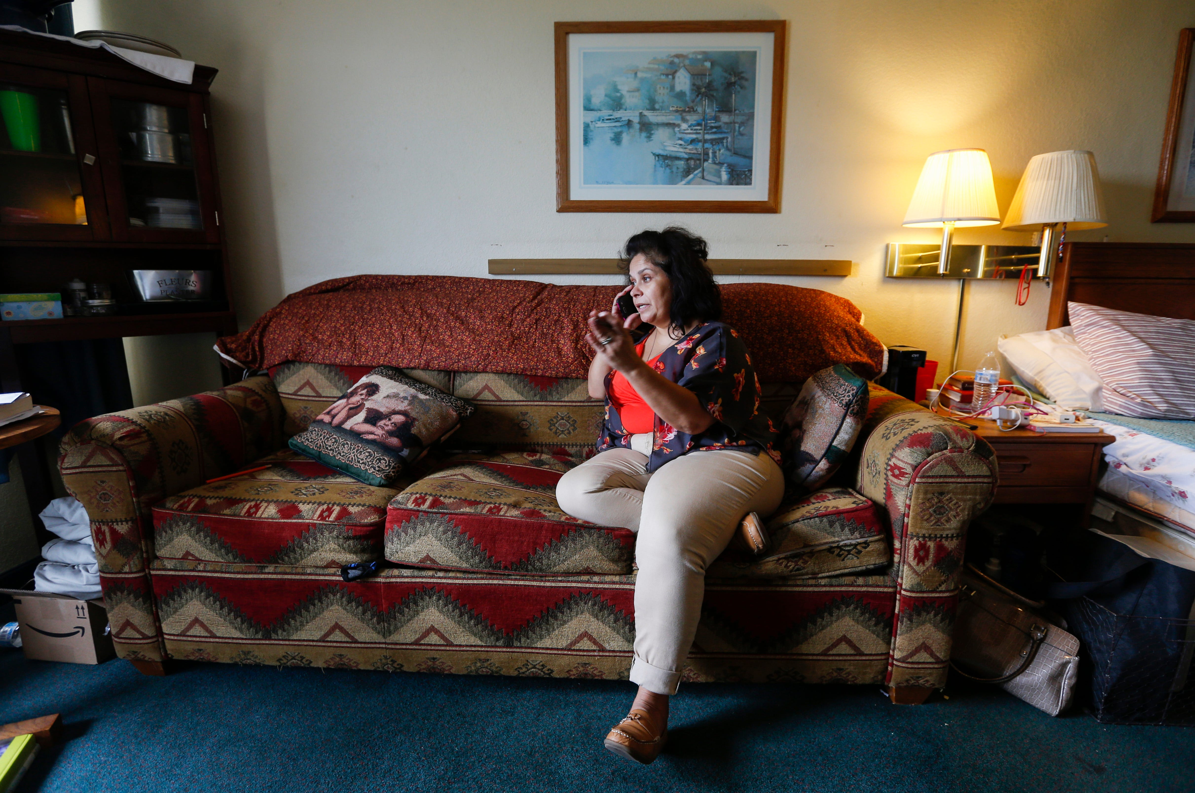 Chrystal Ketterman talks on the phone about a potential job inside of her room at the extended stay hotel she is living in in Branson on Monday, July 30, 2018.