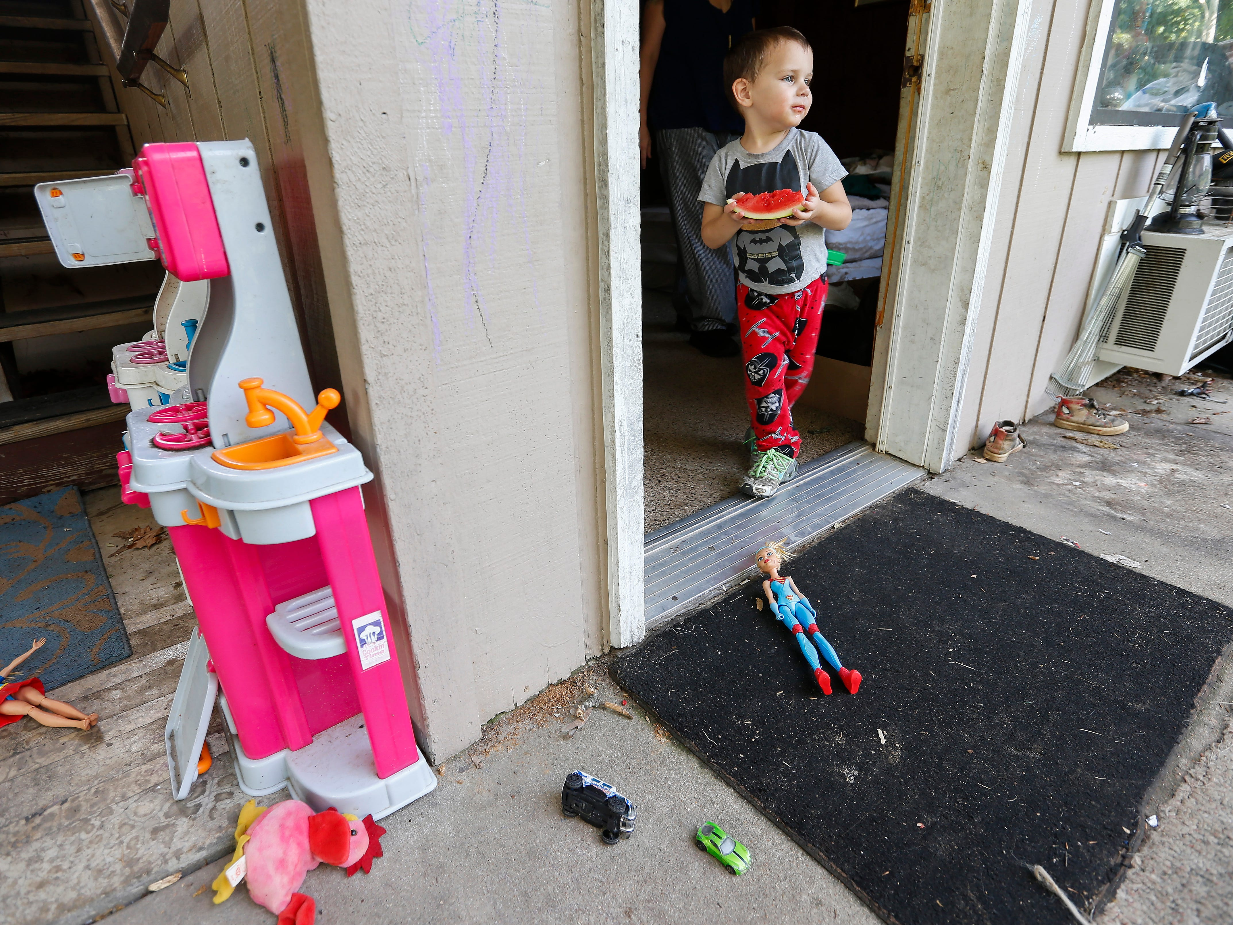 Gabriel Norris, 3, walks out of his family's room with a slice of watermelon at the extended stay hotel they live in in Branson on Wednesday, July 18, 2018. They spend most of their time outside their room in the outdoor seating area they created talking with friends and barbecuing.