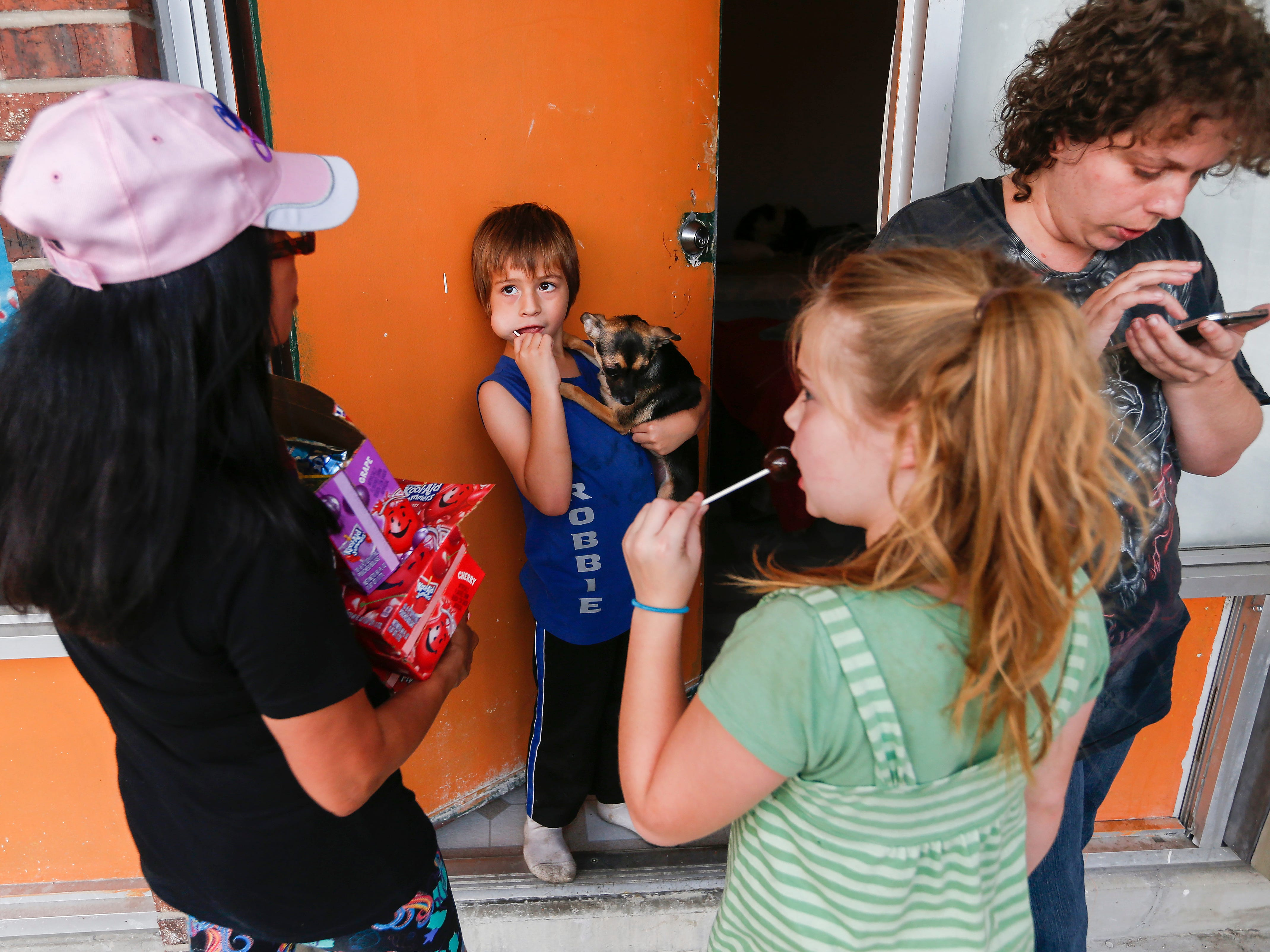 Estrella Wilson, left, a volunteer with Jesus Was Homeless, delivers meals to  Ally Brown, right, and her children Robby, center, and Rizlin at the Branson Plaza on Thursday, July 5, 2018. Jesus Was Homeless volunteers deliver meals to residents in Branson's extended stay hotels every Thursday.