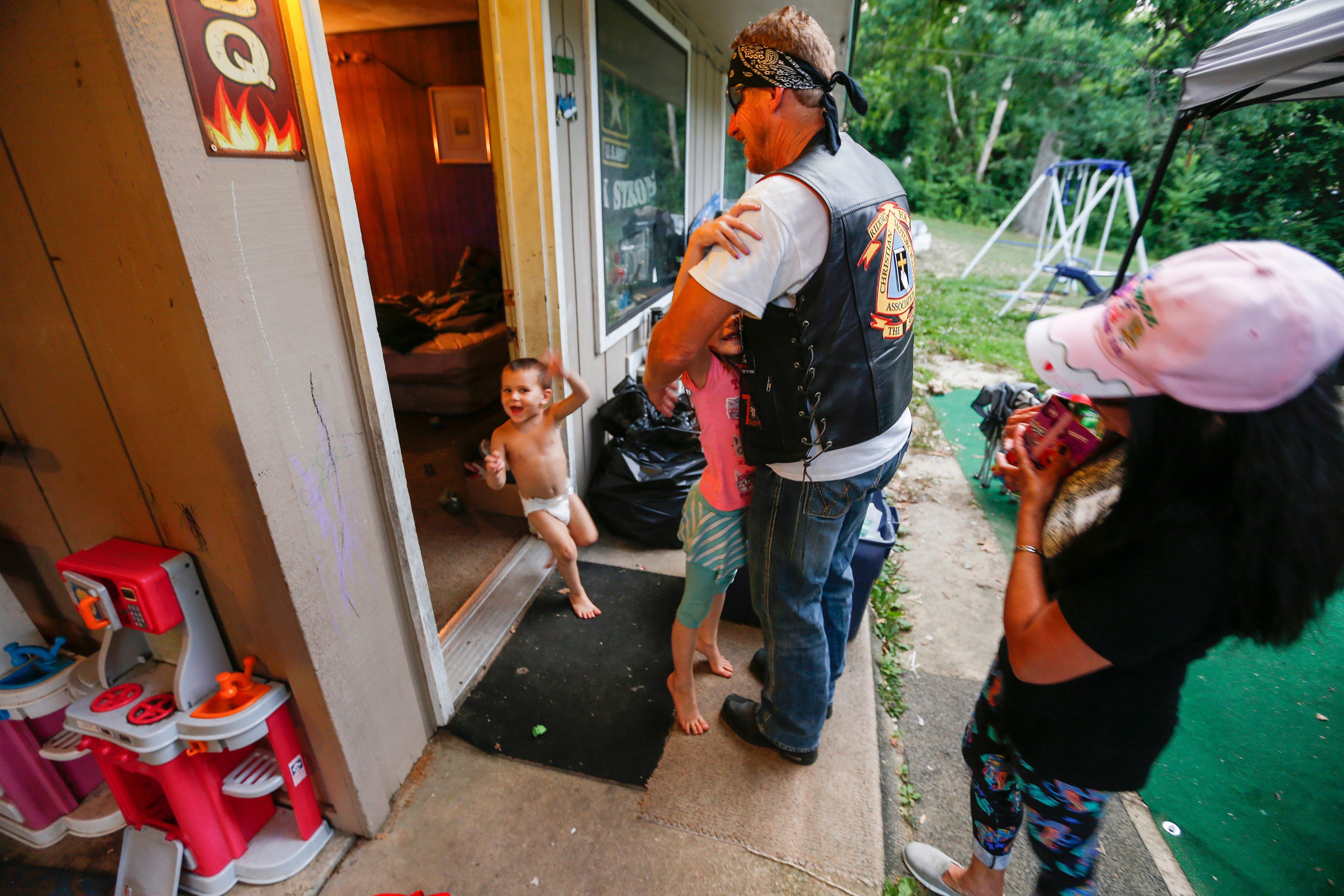 Rick Diamond and Estrella Wilson, volunteers with Jesus Was Homeless, are greeted by Deborah Norris, 6, and her brother Gabriel Norris, 3, on Thursday, July 5, 2018. Jesus Was Homeless volunteers deliver meals to residents in Branson's extended stay hotels every Thursday.
