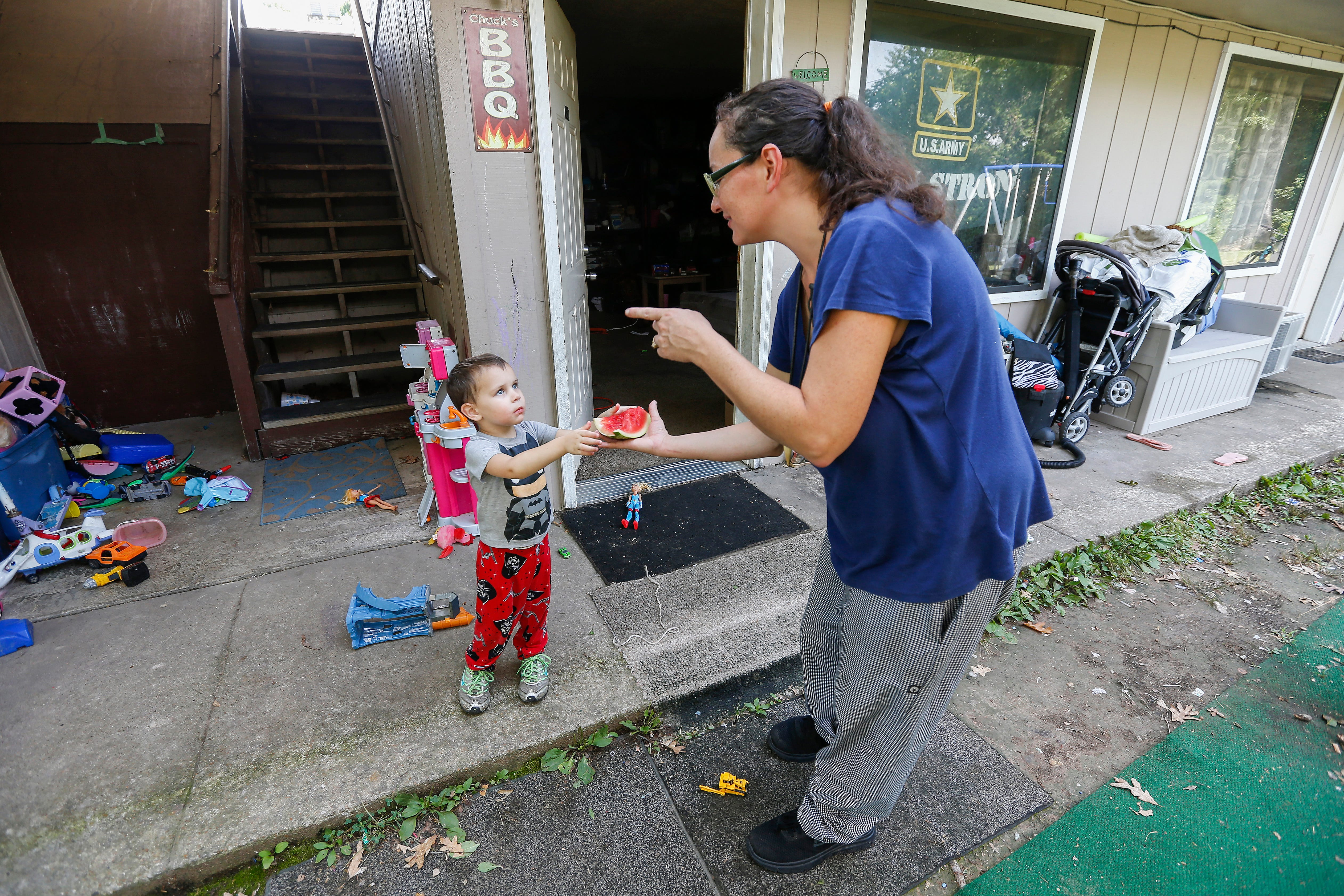Amanda Norris hands a slice of watermelon to her son Gabriel Norris, 3, outside of their room at the extended stay hotel they live in in Branson on Wednesday, July 18, 2018. They spend most of their time outside their room in the outdoor seating area they created talking with friends and barbecuing.