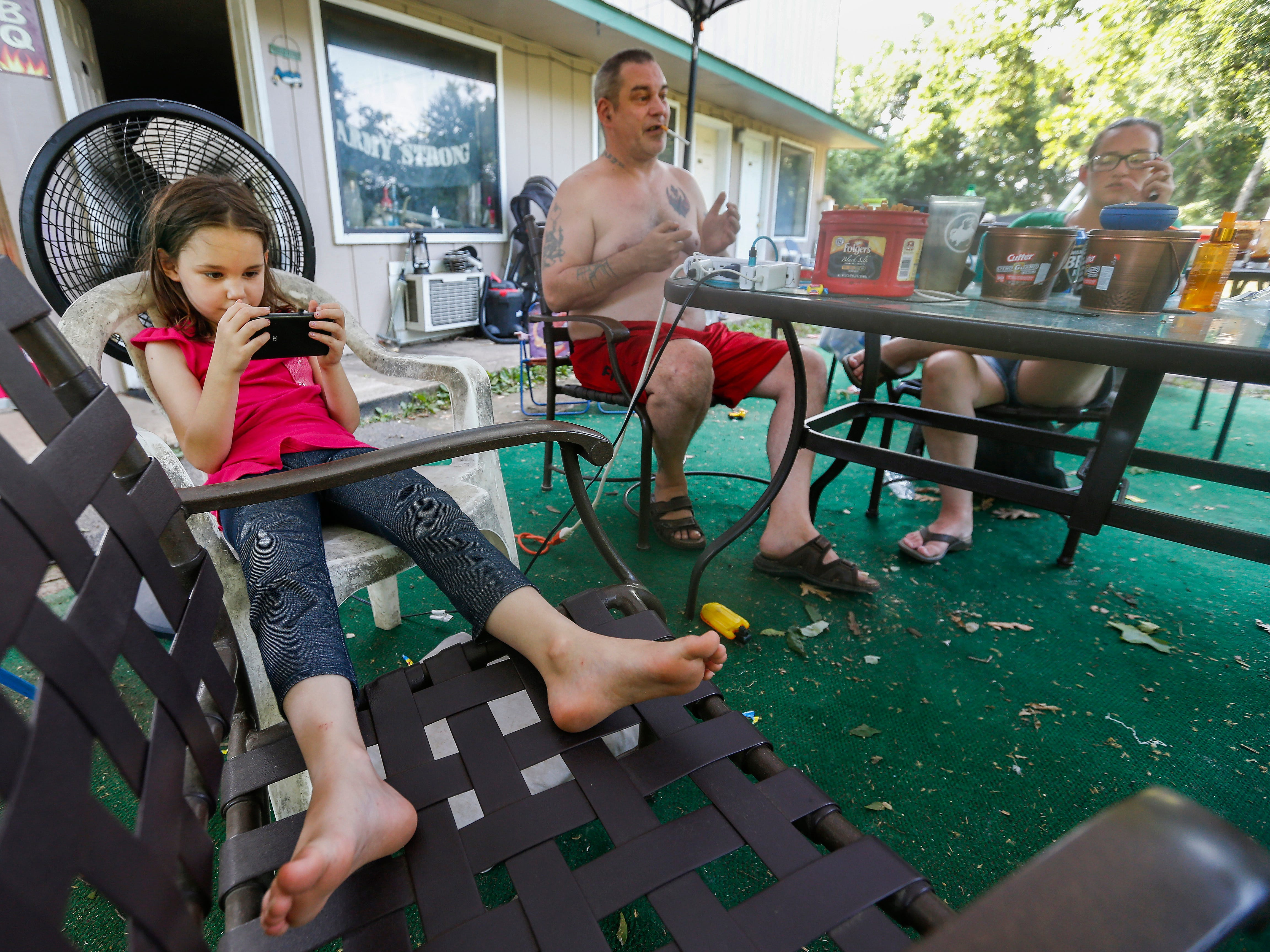 Deborah Norris, 6, watches a video on a cellphone while a fan blows behind her as her parents Chuck Stuedl and Amanda Norris talk with friends while barbecuing outside of their room at the extended stay hotel they live in in Branson on Friday, July 20, 2018.