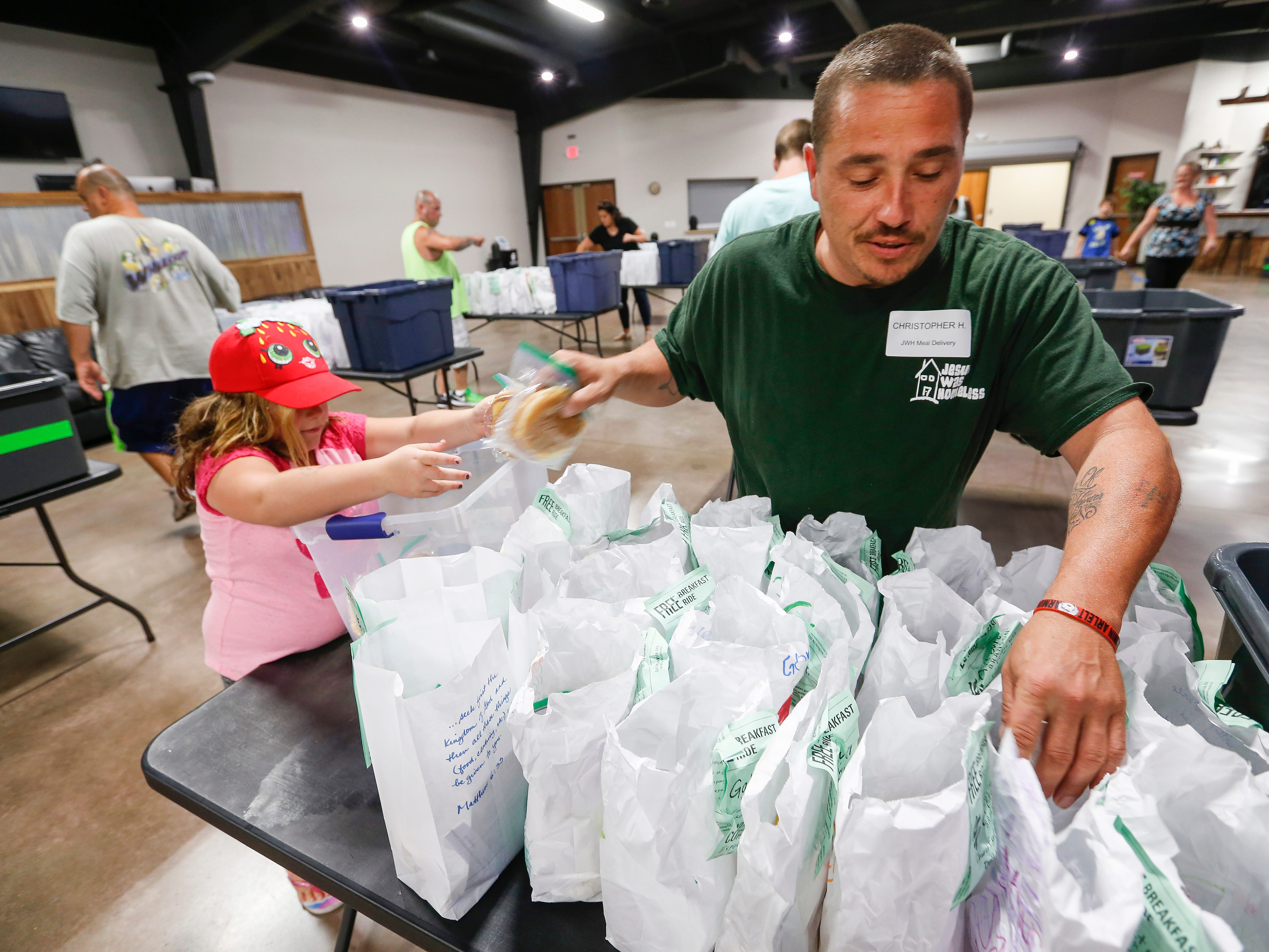 Chris Hunter gets some help from his daughter Raina Hunter, 7, packing meals at Jesus Was Homeless in Branson on Thursday, July 5, 2018.