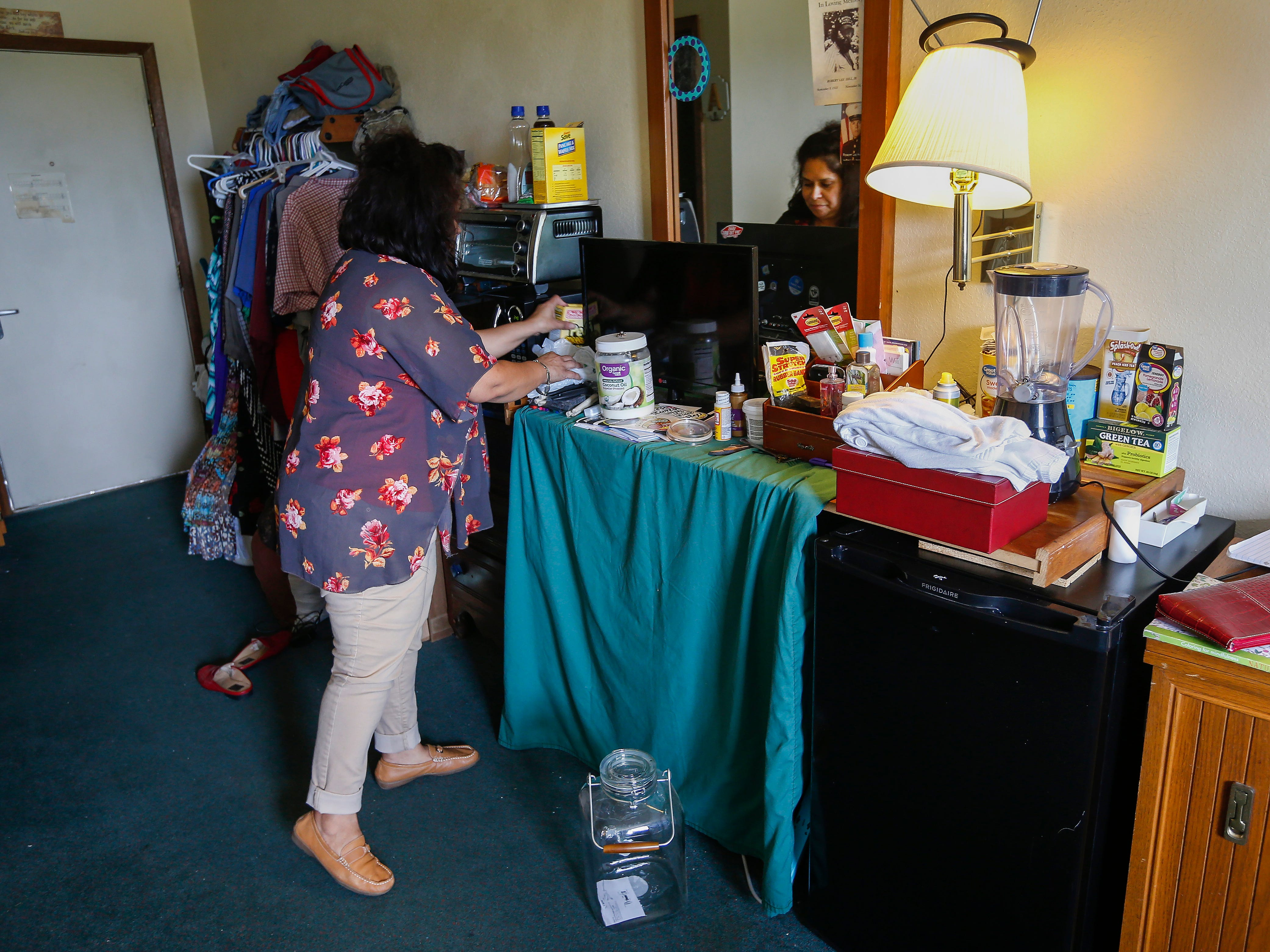 Chrystal Ketterman straightens up inside of her room at the extended stay hotel she is living in in Branson on Monday, July 30, 2018.