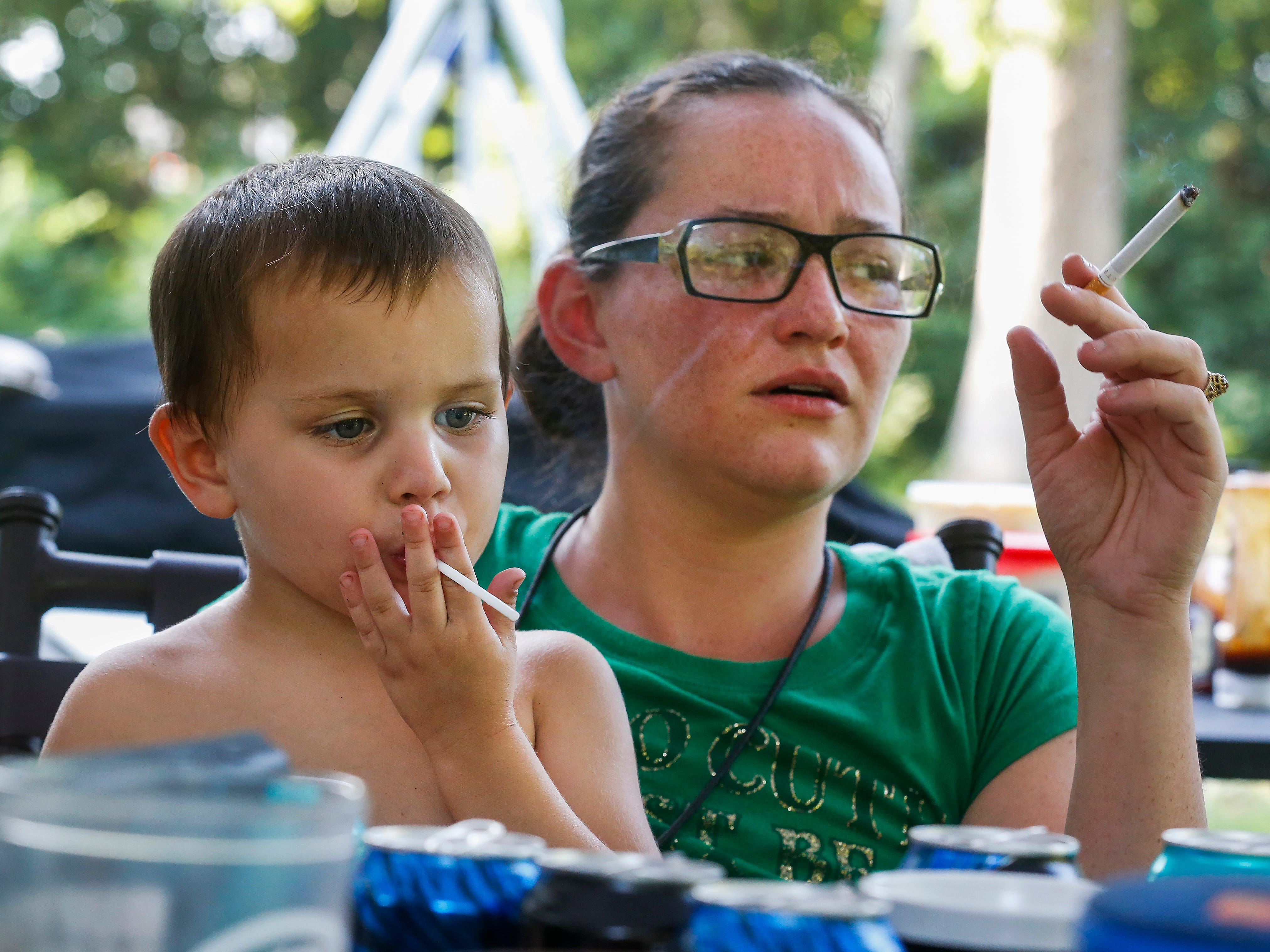 Gabriel Norris, 3, uses the stick from a sucker to imitate his mom Amanda Norris smoking a cigarette while the family barbecued outside of their room at the extended stay hotel they live in in Branson on Friday, July 20, 2018.