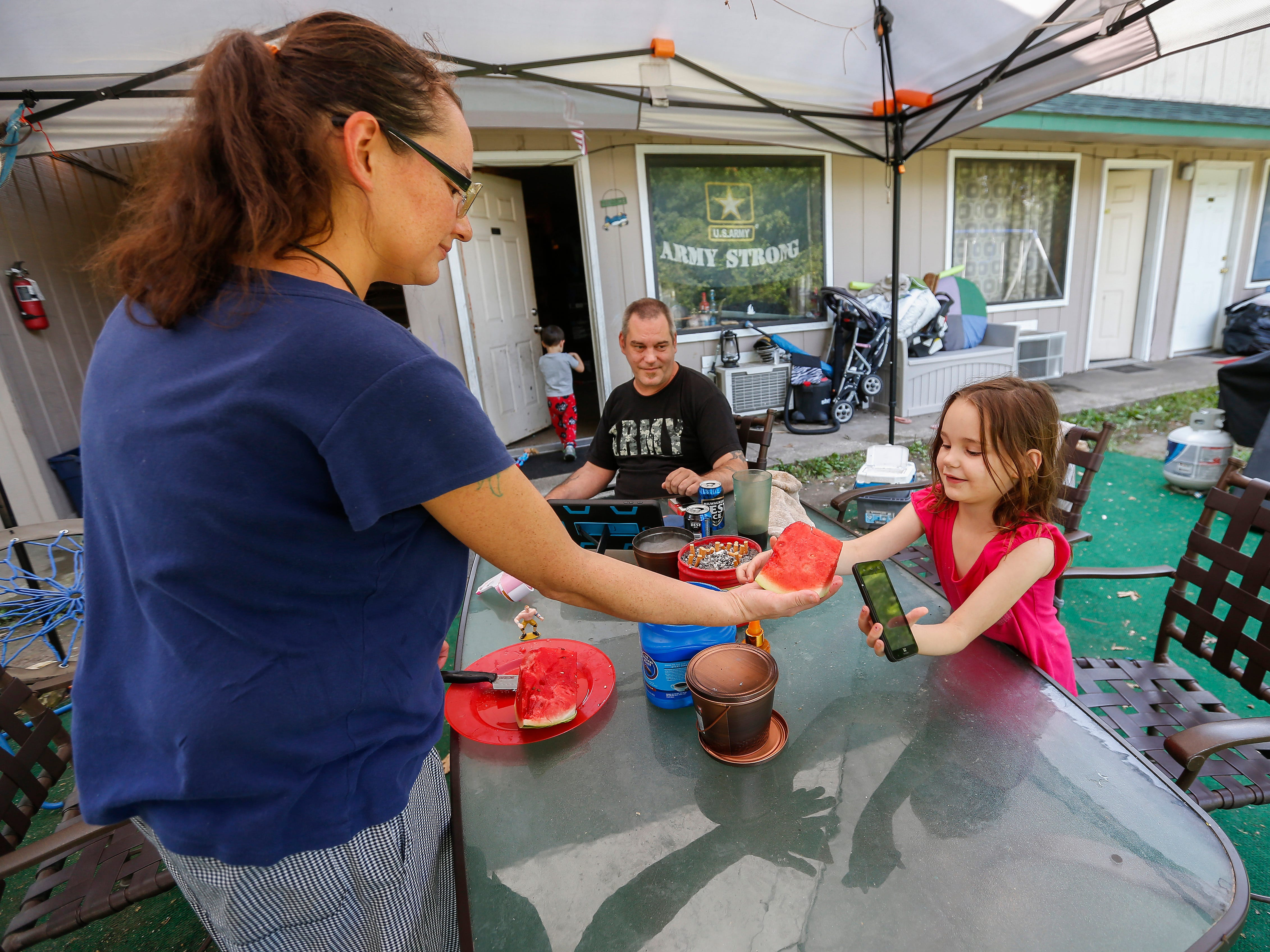 Amanda Norris gives a slice of watermelon to her daughter Deborah Norris, 6, outside of their room at the extended stay hotel they live in in Branson on Wednesday, July 18, 2018. They spend most of their time outside of their room in the outdoor seating area they created talking with friends and barbecuing.