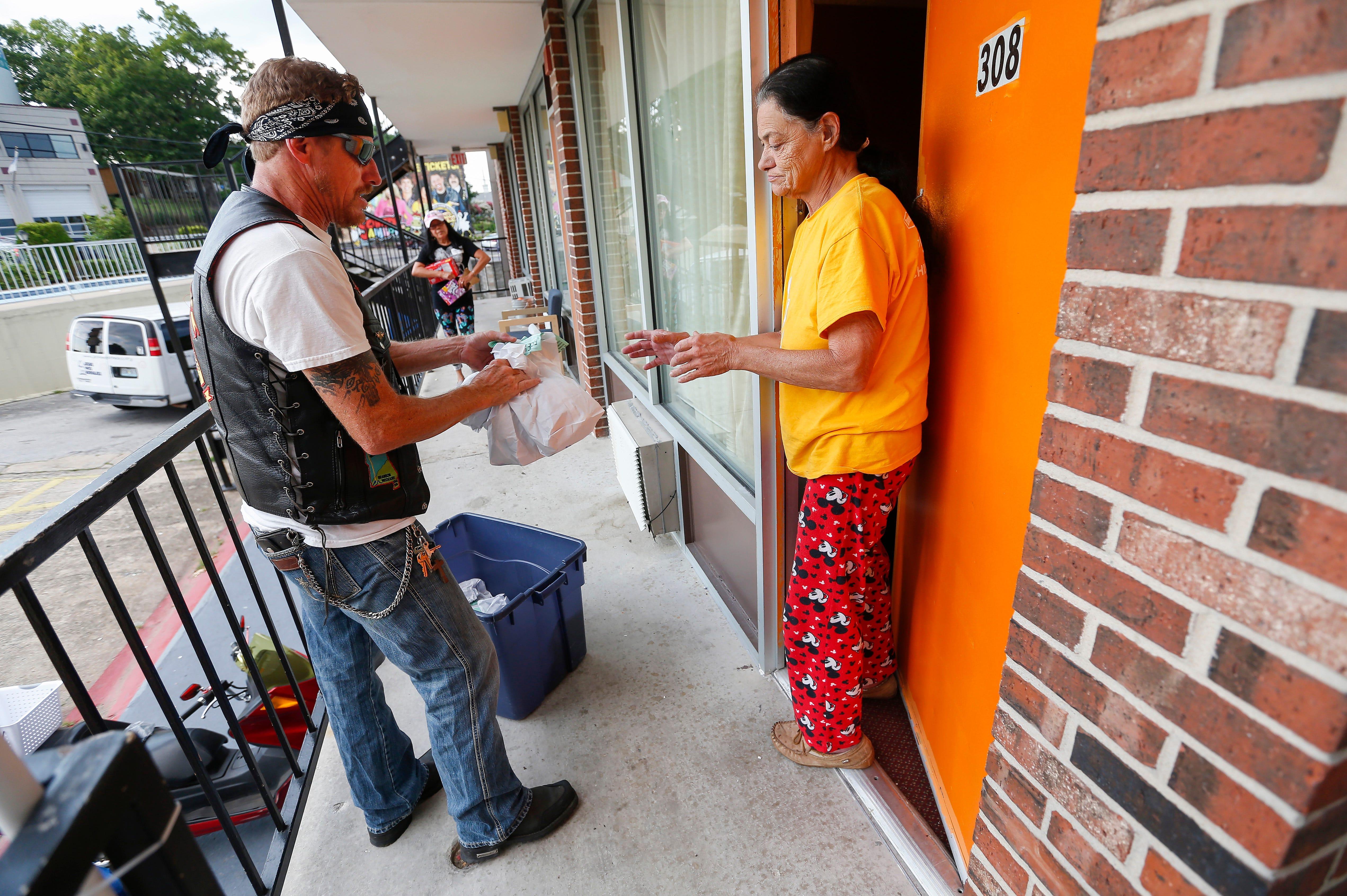 Rick Diamond, a volunteer with Jesus Was Homeless, delivers a meal to Sandy Lucas at the Branson Plaza on Thursday, July 5, 2018. Jesus Was Homeless volunteers deliver meals to residents in Branson's extended stay hotels every Thursday.