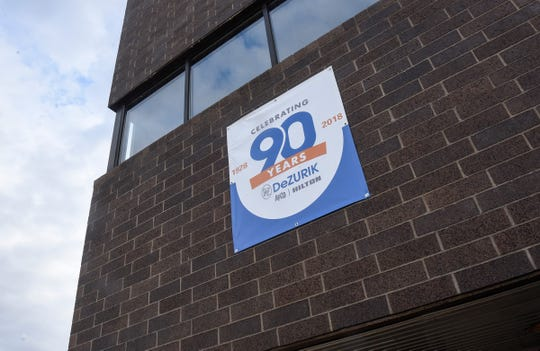 A sign advertises the 90th anniversary of the DeZURIK plant in Sartell.