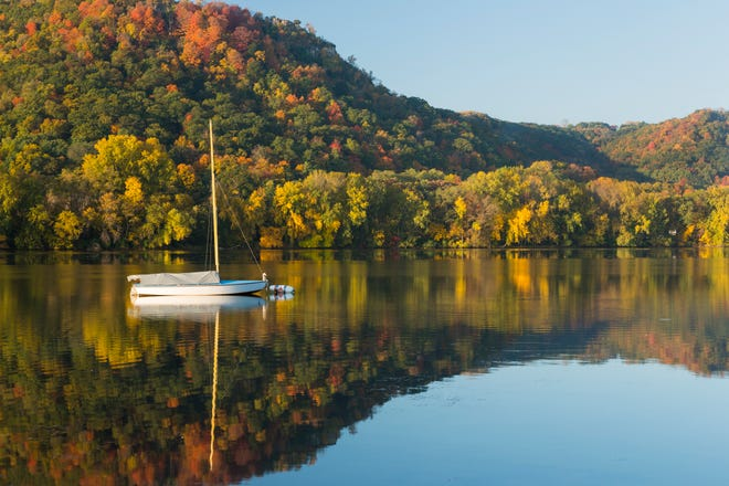 Fall colored trees in the hills with sailboat on calm, reflective Lake Winona.