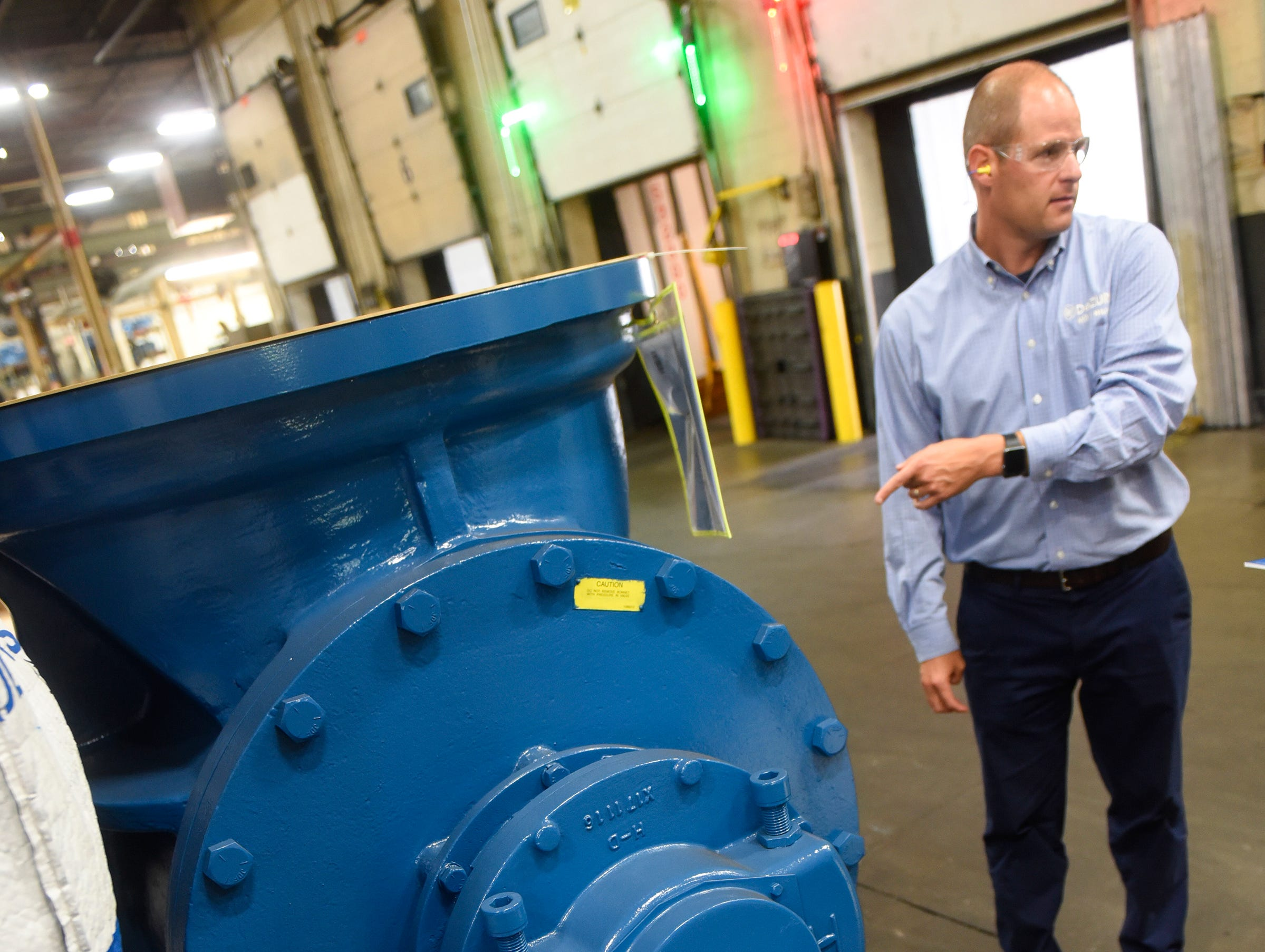 CEO and President Bryan Burns stands next to a large valve on the manufacturing shop floor Monday, Sept. 10, at the DeZURIK plant in Sartell.