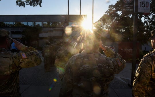 The morning sun outlines ROTC members as they salute during a  Patriot Day flag-raising ceremony Tuesday, Sept. 11, at St. Cloud State University.