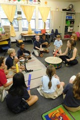 Catherine Miller leads the class in a rhythm exercise with percussion instruments.