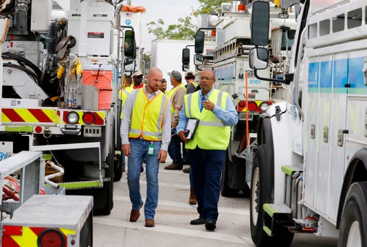 Wade Jollimore (left), Broward County distribution operations leader for Florida Power & Light Company (FPL),  with Darryl Comer, Broward County distribution operations lead for FPL, as they prepare bucket trucks and crews to leave from the West Palm Beach Service Plaza on Florida's Turnpike in Lake Worth Tuesday