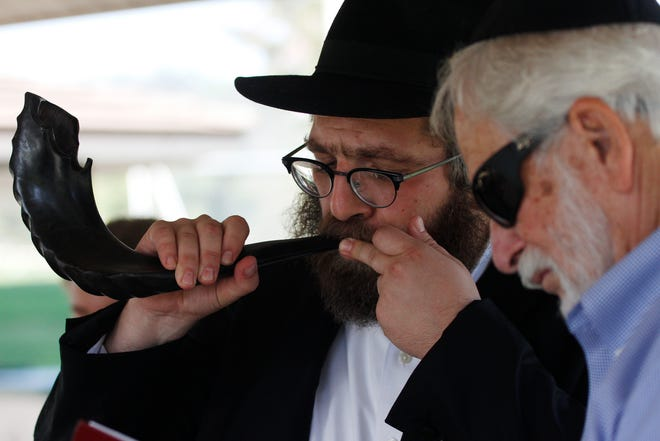 """Rabbi Aryeh Lang blows the shofar as Joel Aaronson reads a prayer during the first """"Shofar in the Park,"""" hosted by the Chabad Jewish Center of Camarillo, on the first day of Rosh Hashana, at Mission Oaks Park in Camarillo on Monday."""