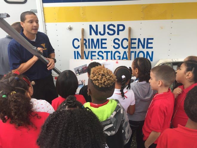 Mennies Elementary students listen to New Jersey State Police Detective Richard Echevarria  talk about the tools  officers use to solve crime during a tribute to heroes on Sept. 11, 2018