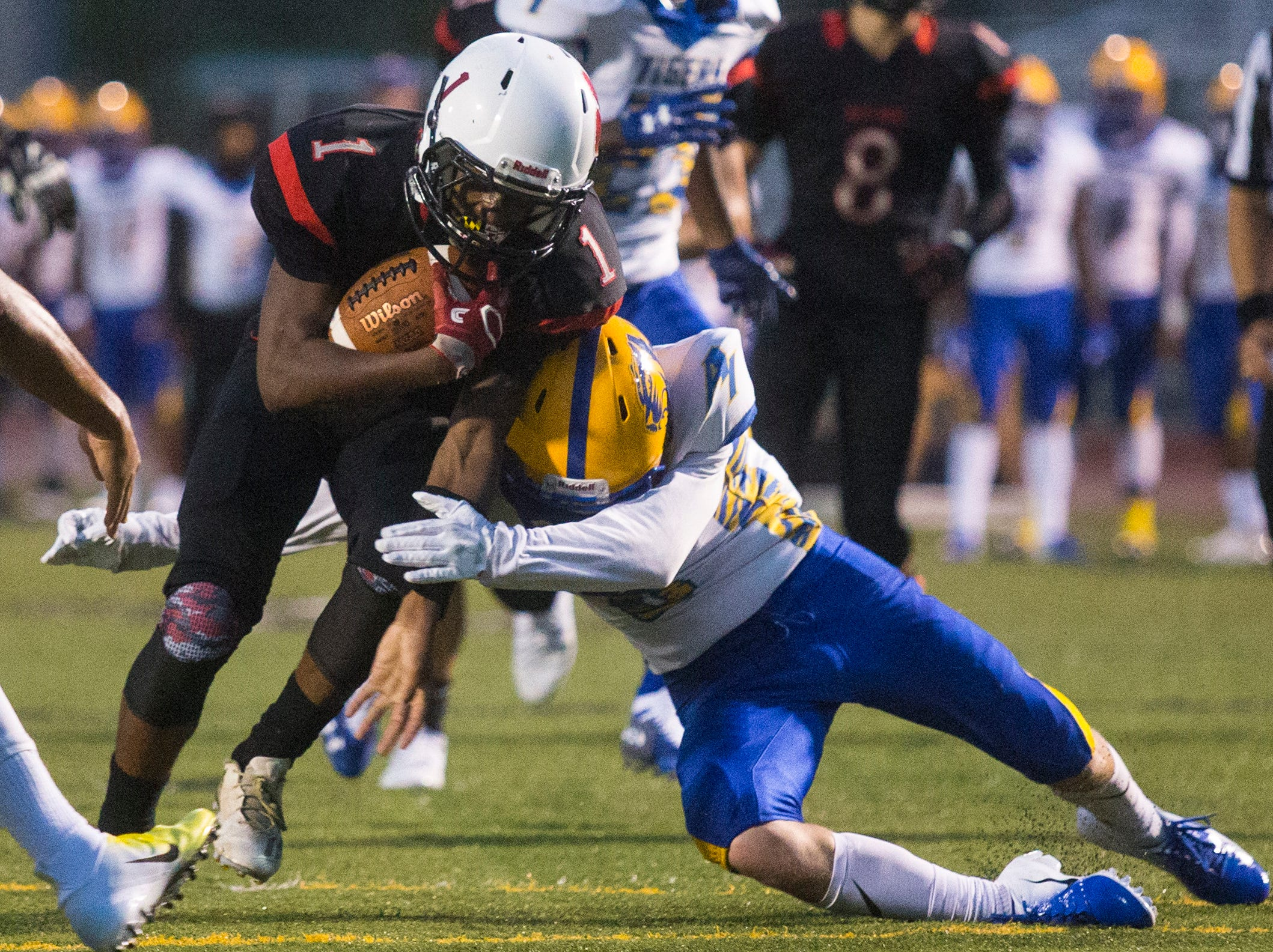 Polytech's Donell Hooker (1) pushes his way through the A.I. du Pont defense Monday night at Appoquinimink High School.