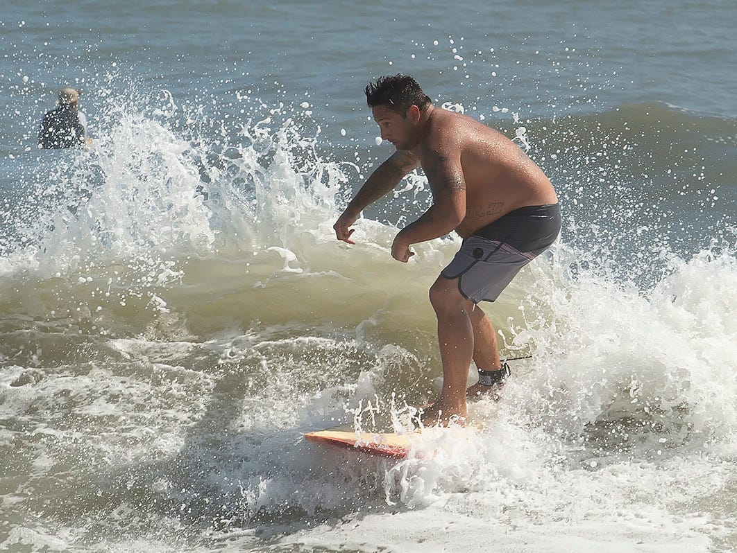 A surfer rides at the Indian River Inlet. Hurricane Florence is causing stormy conditions along the Delaware Beaches.