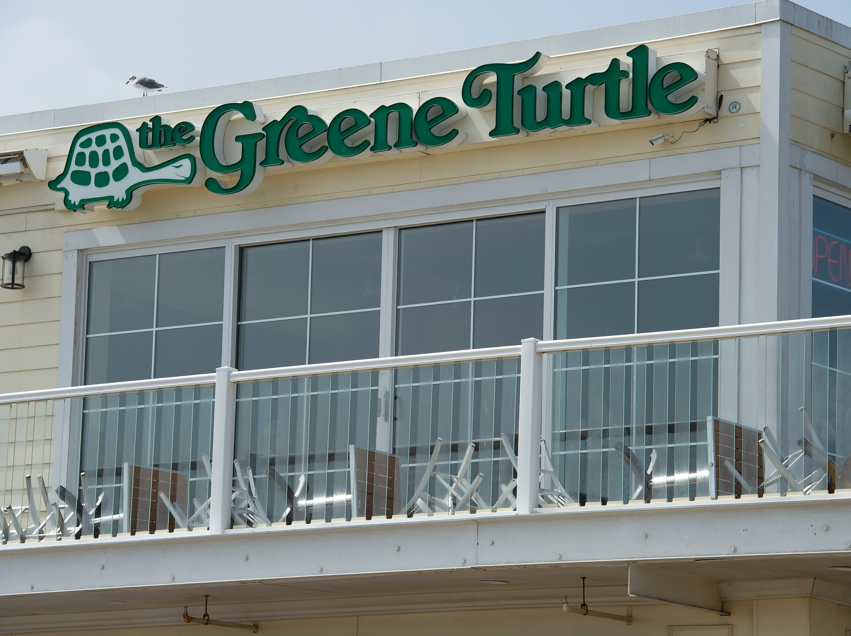 Chairs and tables laying down on the second floor outside seating area at the Greene Turtle in Rehoboth Beach.