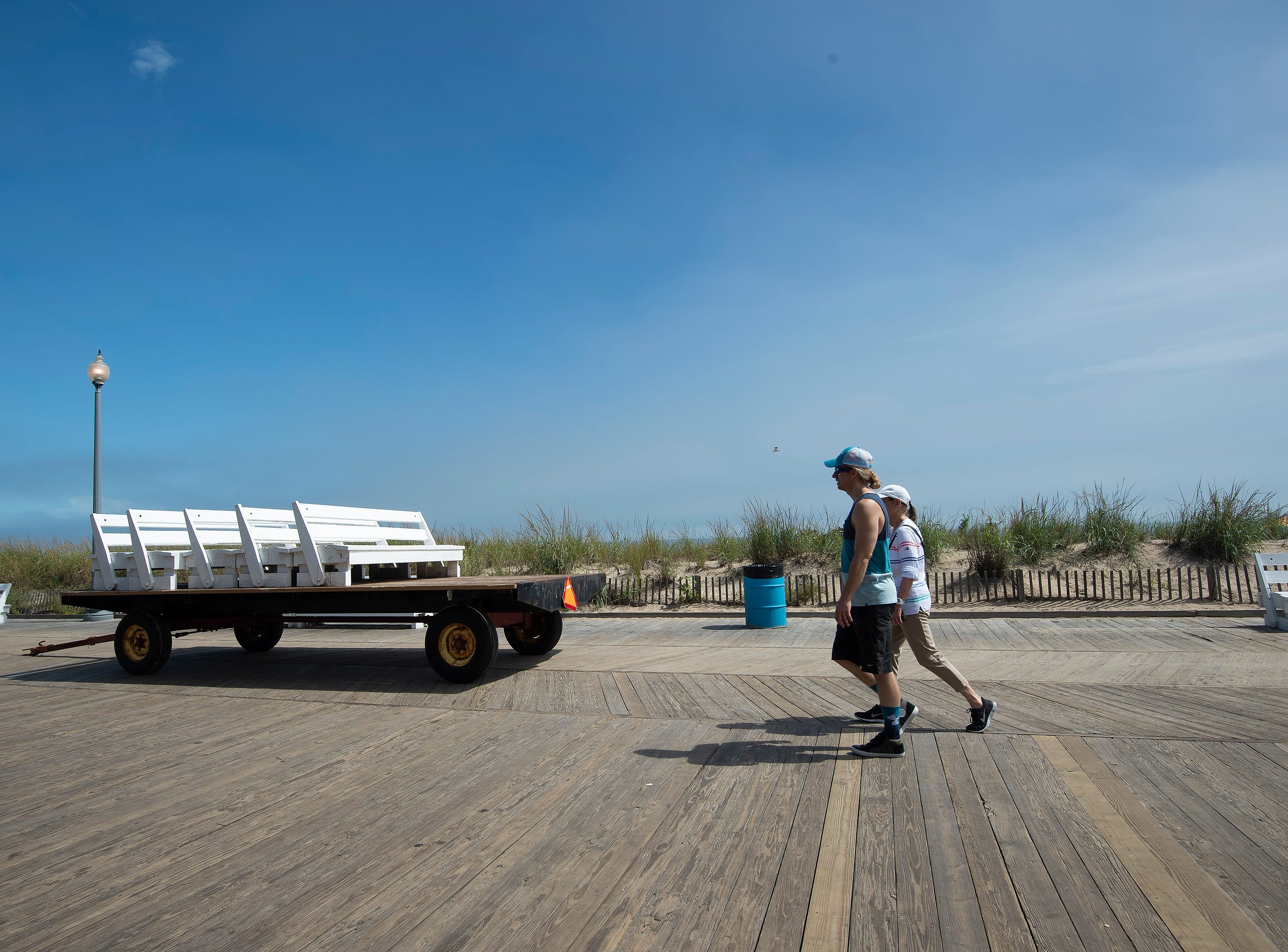 Beachgoers walk next to a trailer of beach benches at Rehoboth Beach.