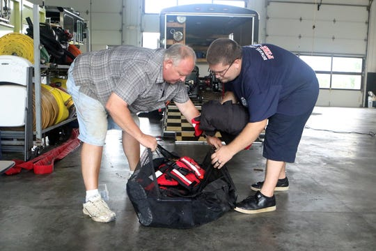Past chief Jeff Morris and six-year Bowers volunteer Ernest Juliano prepare swift water rescue gear for possible use this week.