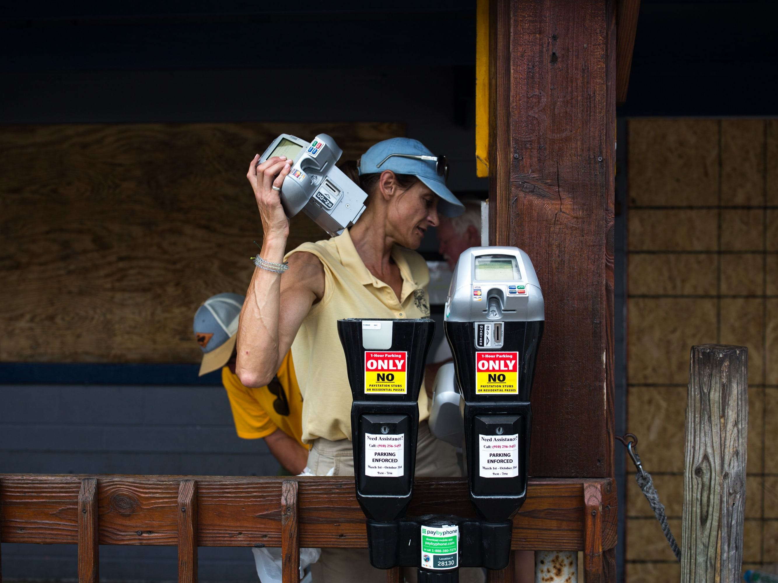 An employee of the Wrightsville Beach Parking office, collects the electronic parts of the parking meters on North Lumina Avenue in Wrightsville Beach, removing the meters in anticipation of Hurricane Florence's high storm surge. - More than a million people were under evacuation orders in the eastern United States Tuesday, where powerful Hurricane Florence threatened catastrophic damage to a region popular with vacationers and home to crucial government institutions. (Photo by Logan CYRUS / AFP)LOGAN CYRUS/AFP/Getty Images ORIG FILE ID: AFP_1908LM