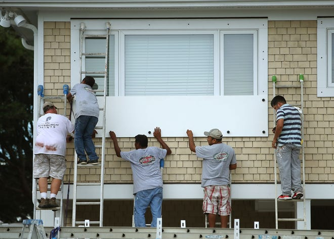 WRIGHTSVILLE BEACH, NC - SEPTEMBER 11:  Workers board up a home while preparing for the arrival of Hurricane Florence on September 11, 2018 in Wrightsville Beach, United States. Hurricane Florence is expected on Friday possibly as a category 4 storm along the Virginia, North Carolina and South Carolina coastline.  (Photo by Mark Wilson/Getty Images) ORG XMIT: 775225768 ORIG FILE ID: 1031464054