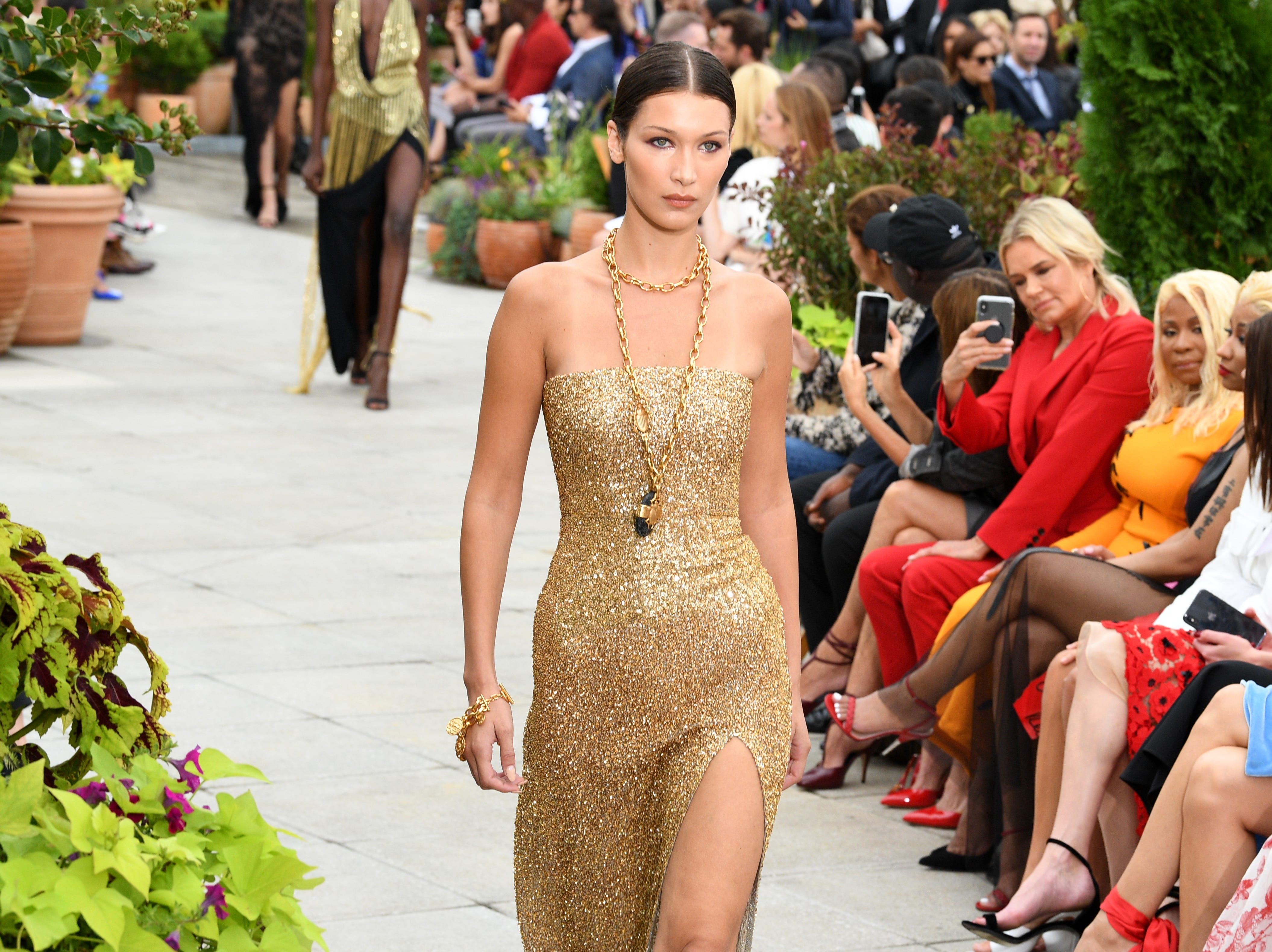 New York Fashion Week continues! Day 7 brought bold, glamorous looks from Oscar De La Renta. Here, Bella Hadid walks the runway in a golden gown Tuesday.