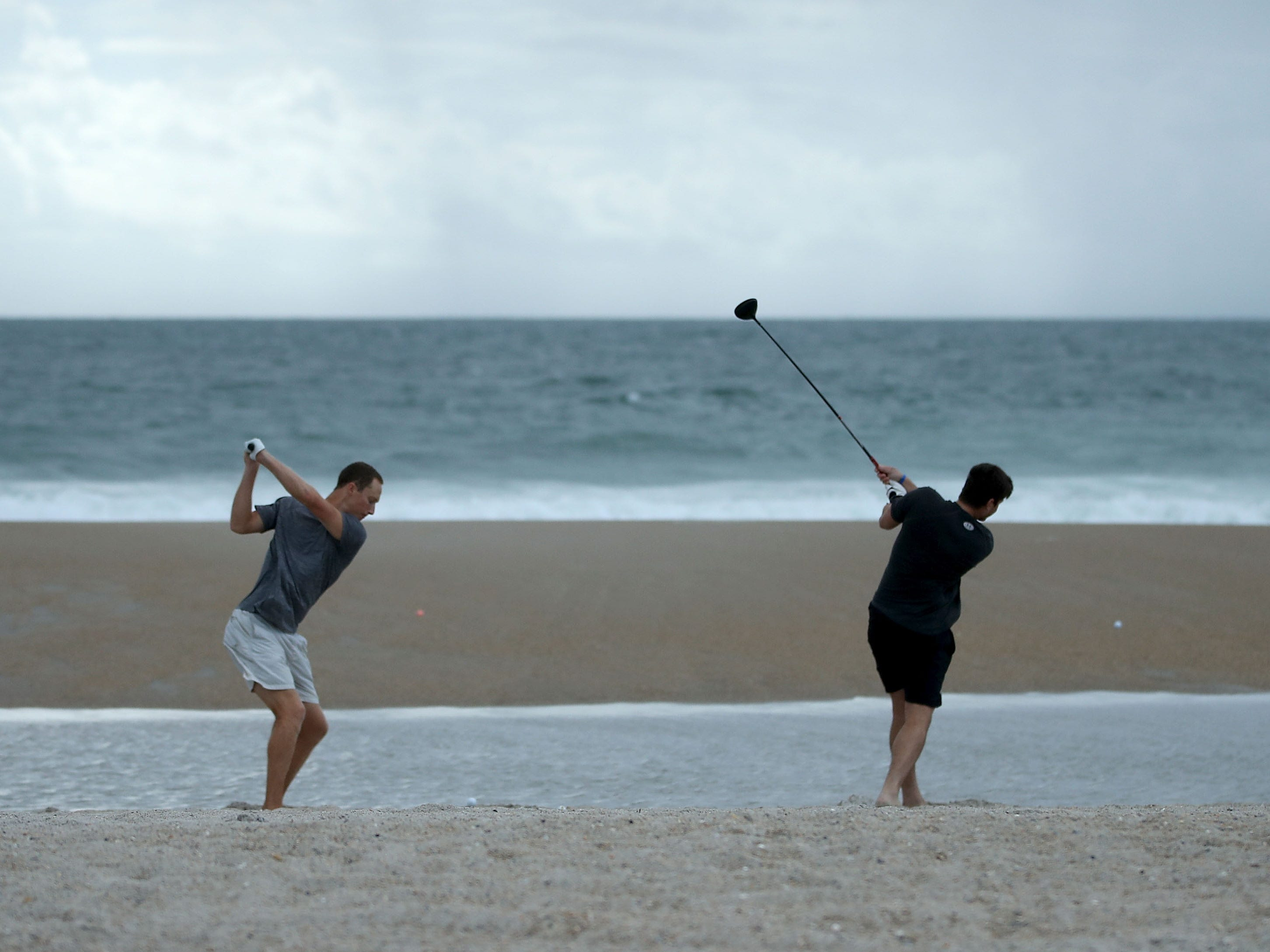 WRIGHTVILLE BEACH, NC- SEPTEMBER 11: Jacob Whitehead (L) and Matt Jones hit golf balls into the surf as Hurricane Florence approaches, on September 11, 2018 in Wrightsville Beach, United States. Hurricane Florence is expected on Friday possibly as a category 4 storm along the Virginia, North Carolina and South Carolina coastline.  (Photo by Mark Wilson/Getty Images) ORG XMIT: 775225768 ORIG FILE ID: 1031308814