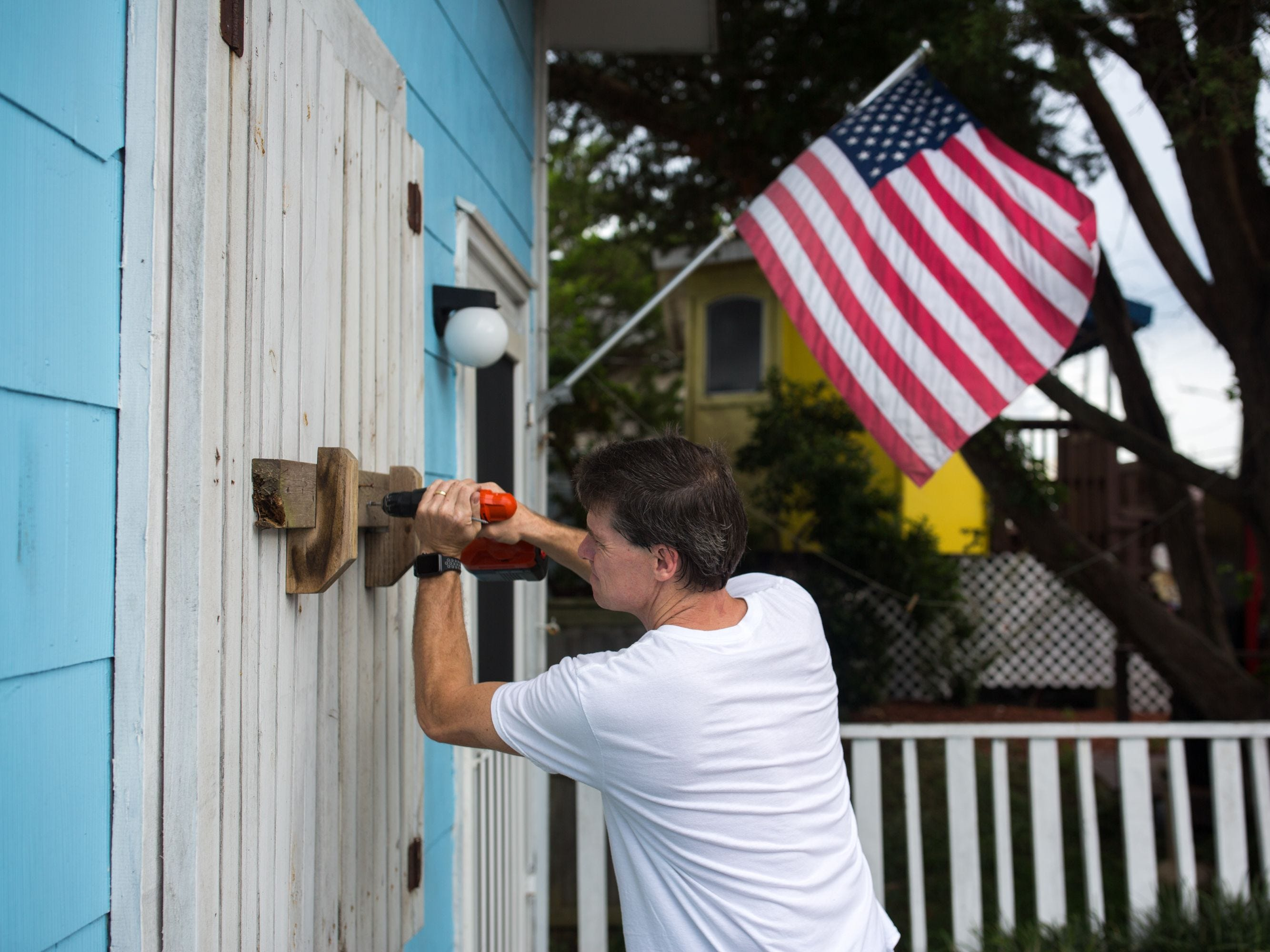 A man helps board up Aussie Island surf shop in anticipation of Hurricane Florence's high storm surge. - More than a million people were under evacuation orders in the eastern United States Tuesday, where powerful Hurricane Florence threatened catastrophic damage to a region popular with vacationers and home to crucial government institutions. (Photo by Logan CYRUS / AFP)LOGAN CYRUS/AFP/Getty Images ORIG FILE ID: AFP_1908LS