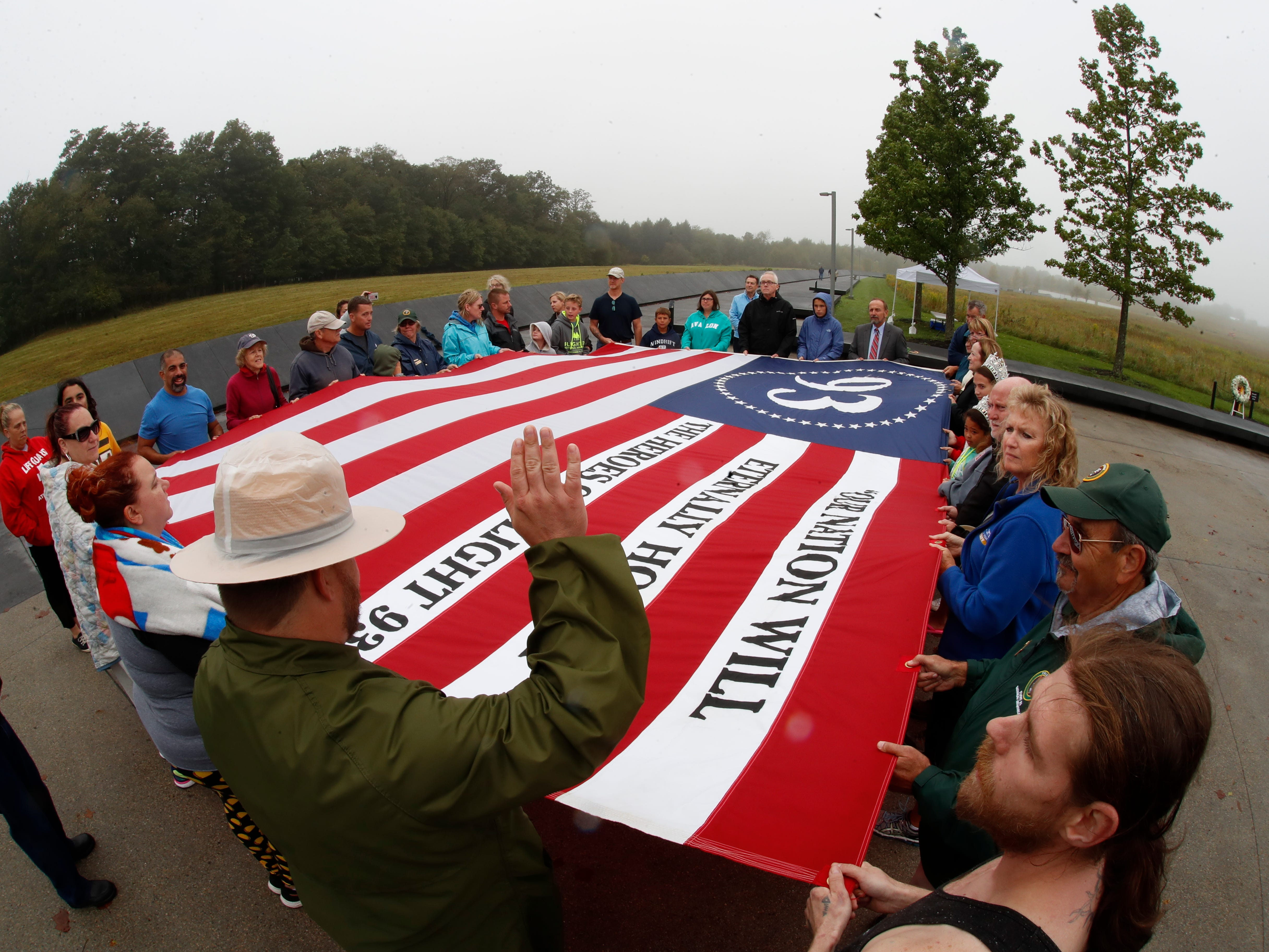 Visitors to the Flight 93 National Memorial in Shanksville, Pa., participate in a sunset memorial service on Monday, Sept. 10, 2018, as the nation marks the 17th anniversary of the Sept. 11, 2001 attacks. (AP Photo/Gene J. Puskar) ORG XMIT: PAGP105
