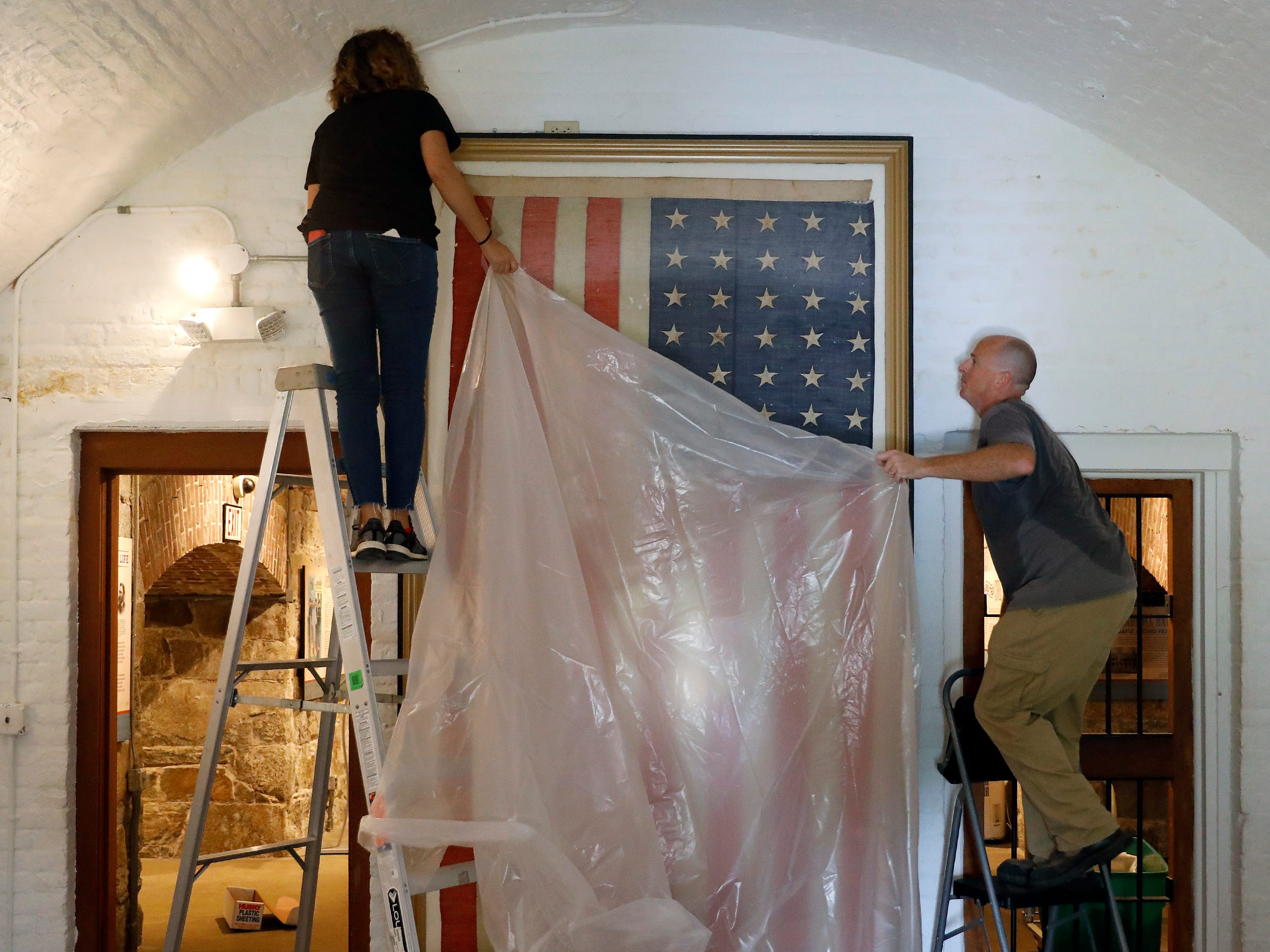 Veronica Gallardo, left, and Robert Kelly place a plastic tarp over the American Flag that hung in the cell of Jefferson Davis inside the Casemate Museum on Fort Monroe, Tuesday, Sept. 11, 2018, in Hampton, Va. The staff is preparing for rising waters and other possible flooding due to Hurricane Florence.