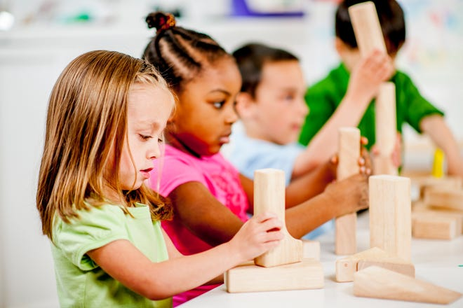 A multi-ethnic group of preschool age students building a constructing shapes and towers with wood blocks in their classroom at school.