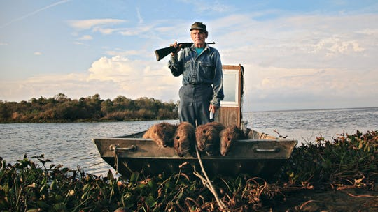 "Thomas Gonzales shows off his slain nutria while defending Delacroix Island in ""Rodents of Unusual Size."""