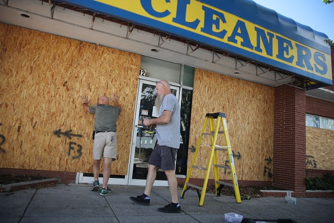 Michael Schwartz, left, and Jay Schwartz secure plywood over the windows of their business ahead of the arrival of Hurricane Florence on September 11, 2018 in Myrtle Beach, South Carolina.