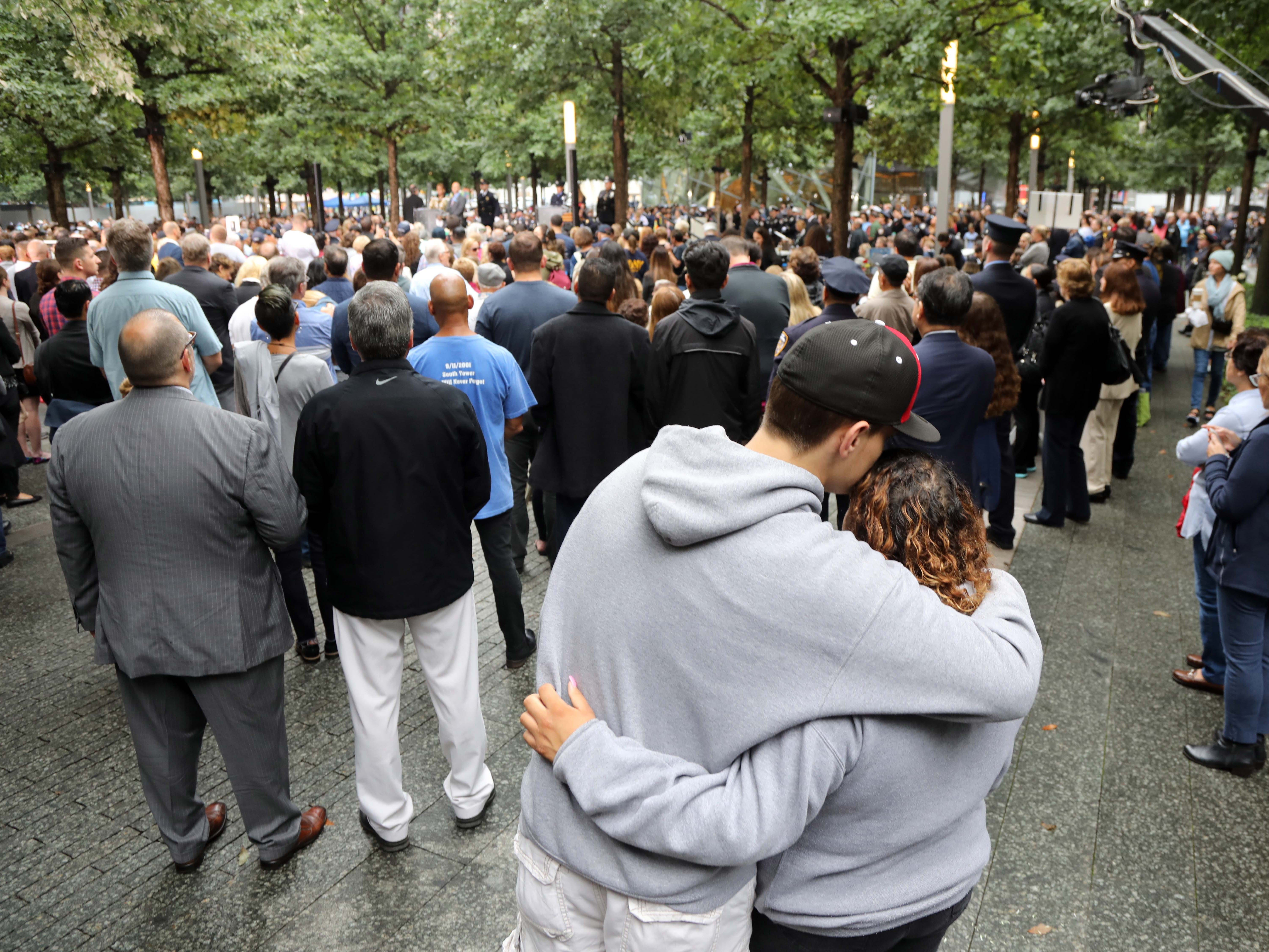 A couple hug as they listen to the names of those who died on 9/11 during ceremonies at the National September 11 Memorial, Sept. 11, 2018, in New York.
