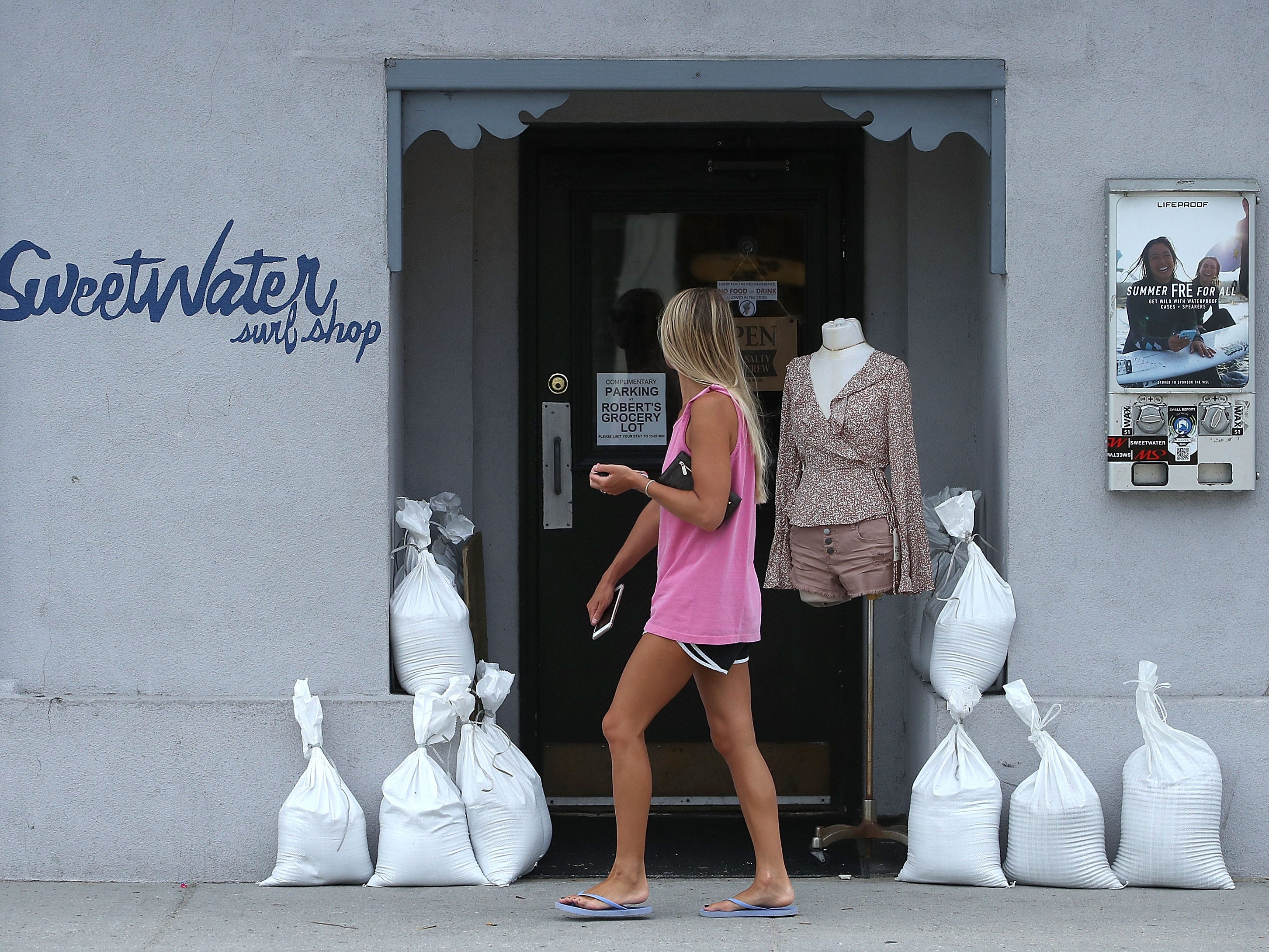 WRIGHTSVILLE BEACH, NC- SEPTEMBER 11: A women walks past a local shop that is prepared for the arrival of Hurricane Florence on September 11, 2018 in Wrightsville Beach, United States. Hurricane Florence is expected on Friday possibly as a category 4 storm along the Virginia, North Carolina and South Carolina coastline.  (Photo by Mark Wilson/Getty Images) ORG XMIT: 775225768 ORIG FILE ID: 1031464342
