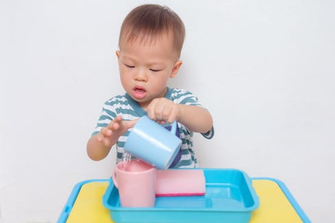 Kids at a Montessori preschool ate off of ceramic plates at snack time, which they then washed in soapy water and placed in a drying tub nearby.