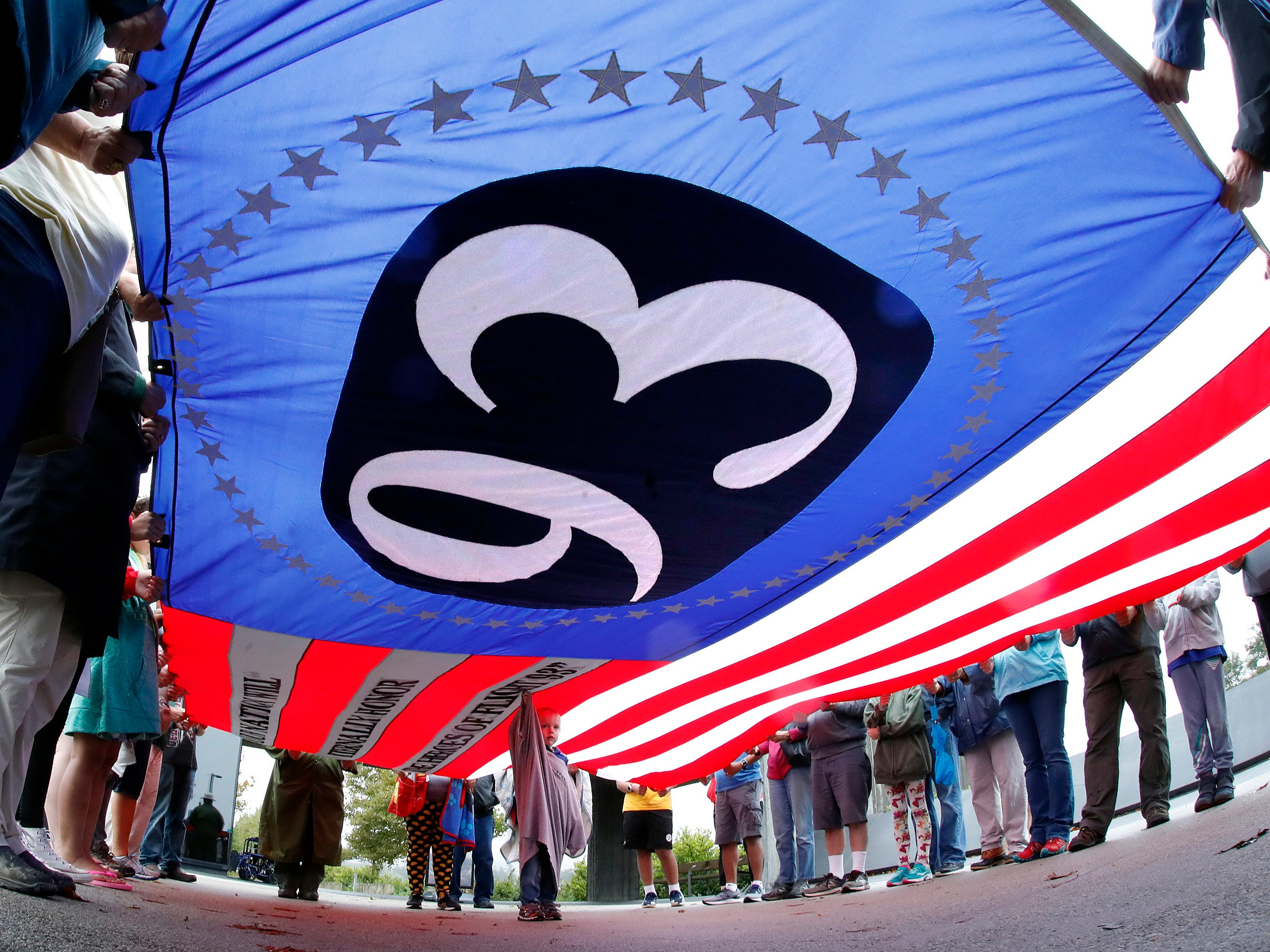 Visitors to the Flight 93 National Memorial in Shanksville, Pa., hold a giant Flight 93 flag during a moment of remembrance Monday, Sept. 10, 2018, as the nation marks the 17th anniversary of the Sept. 11, 2001, attacks. (AP Photo/Gene J. Puskar) ORG XMIT: PAGP101