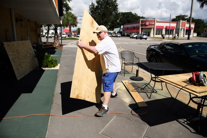 Lee Dorton, owner of Infused Olive in North Myrtle Beach, carries a large piece of plywood over to his business on Sept. 11, 2018.