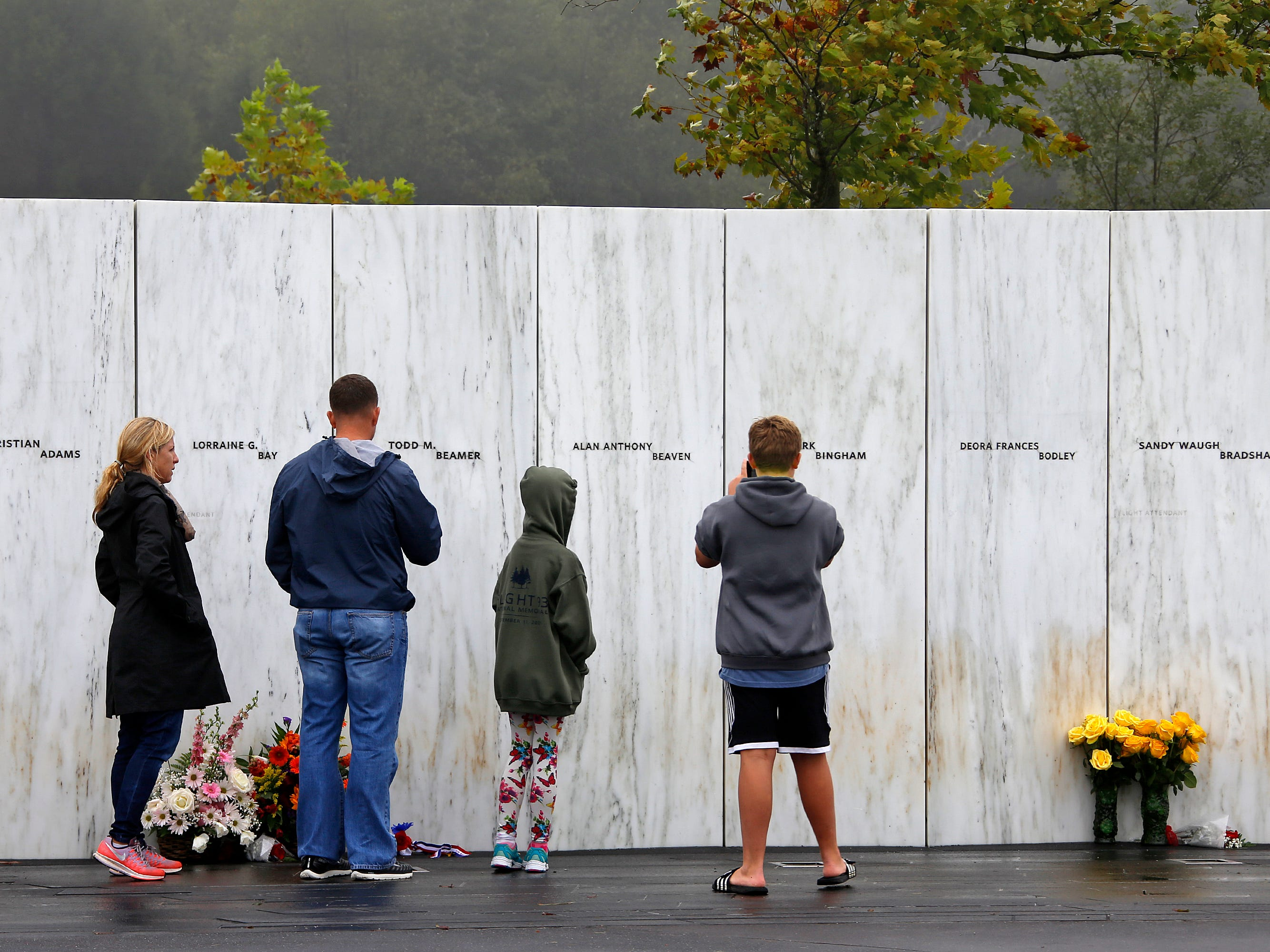 Visitors to the Flight 93 National Memorial in Shanksville, Pa., participate in a sunset memorial service on Monday, Sept. 10, 2018, as the nation marks the 17th anniversary of the Sept. 11, 2001 attacks. (AP Photo/Gene J. Puskar) ORG XMIT: PAGP104
