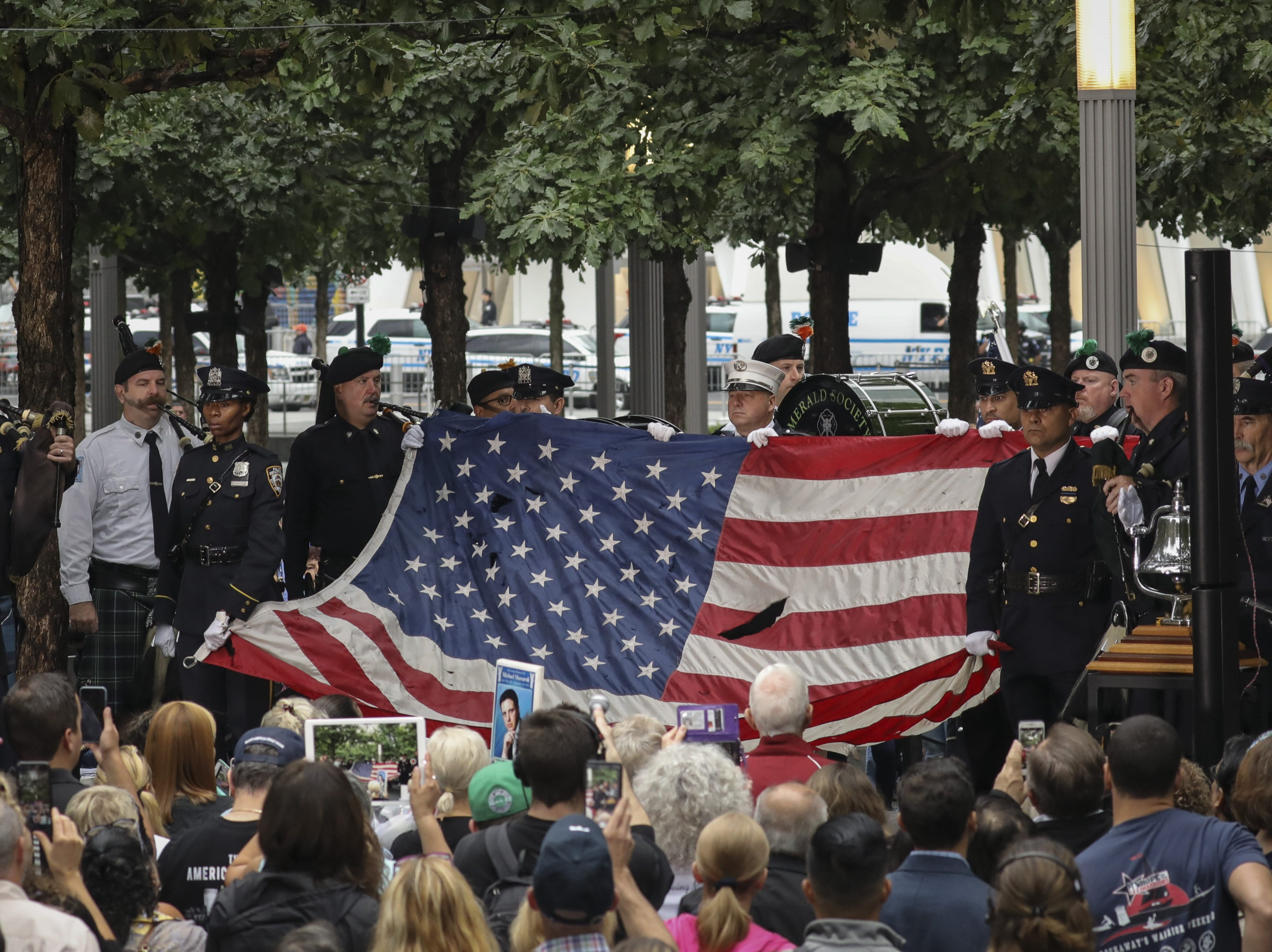 Firefighters hold up a flag that flew at the World Trade Center at the start of a commemoration ceremony in New York.