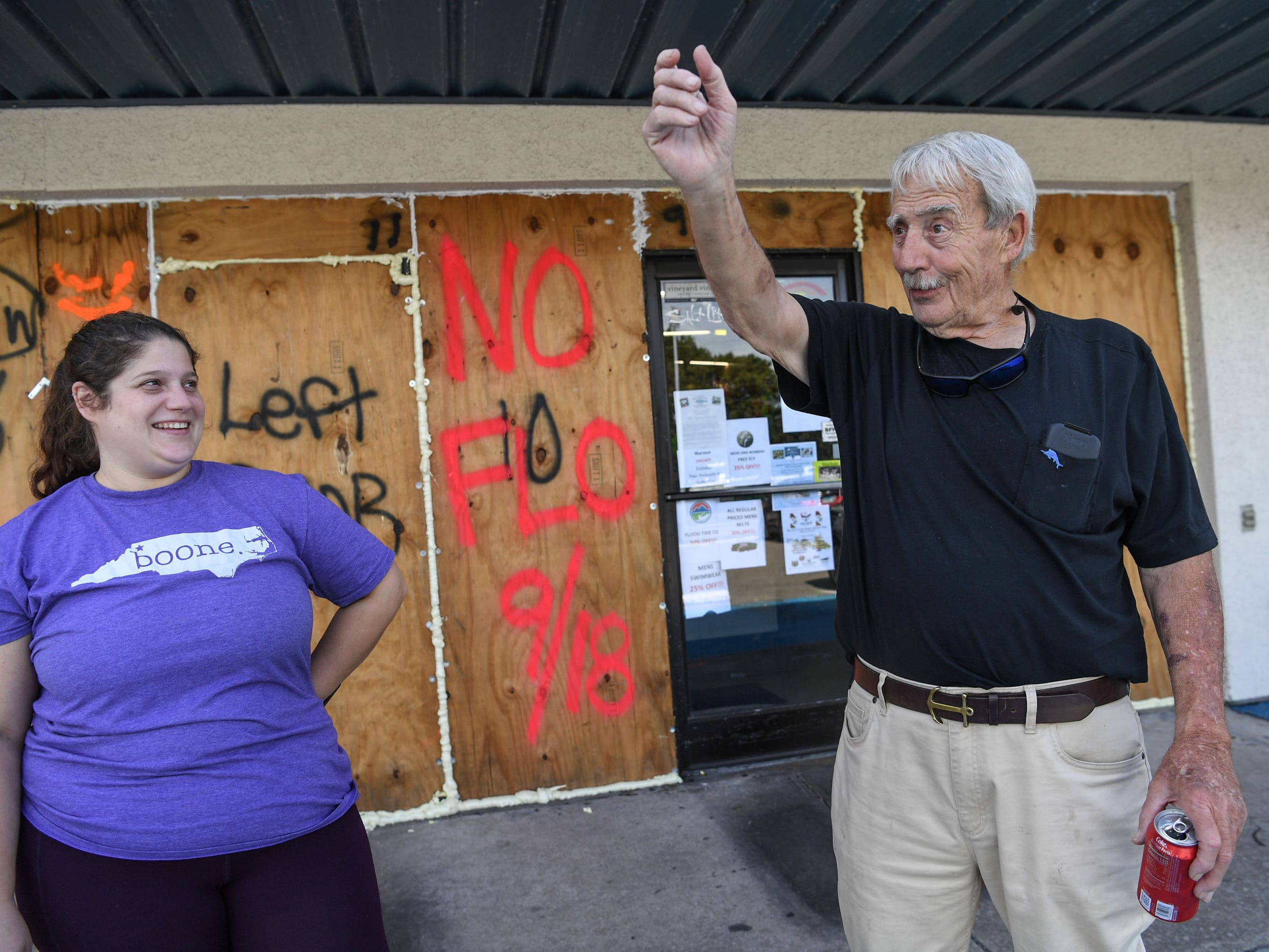 Meredith Reddick, left, and her father Gordon Reddick, owner of Redix store, talk about debris flying through the air and the need for plywood boards covering his windows, on Tuesday, Sept. 11, 2018. Reddick has used the same boards since 1993, and wrote names for each storm ever since.