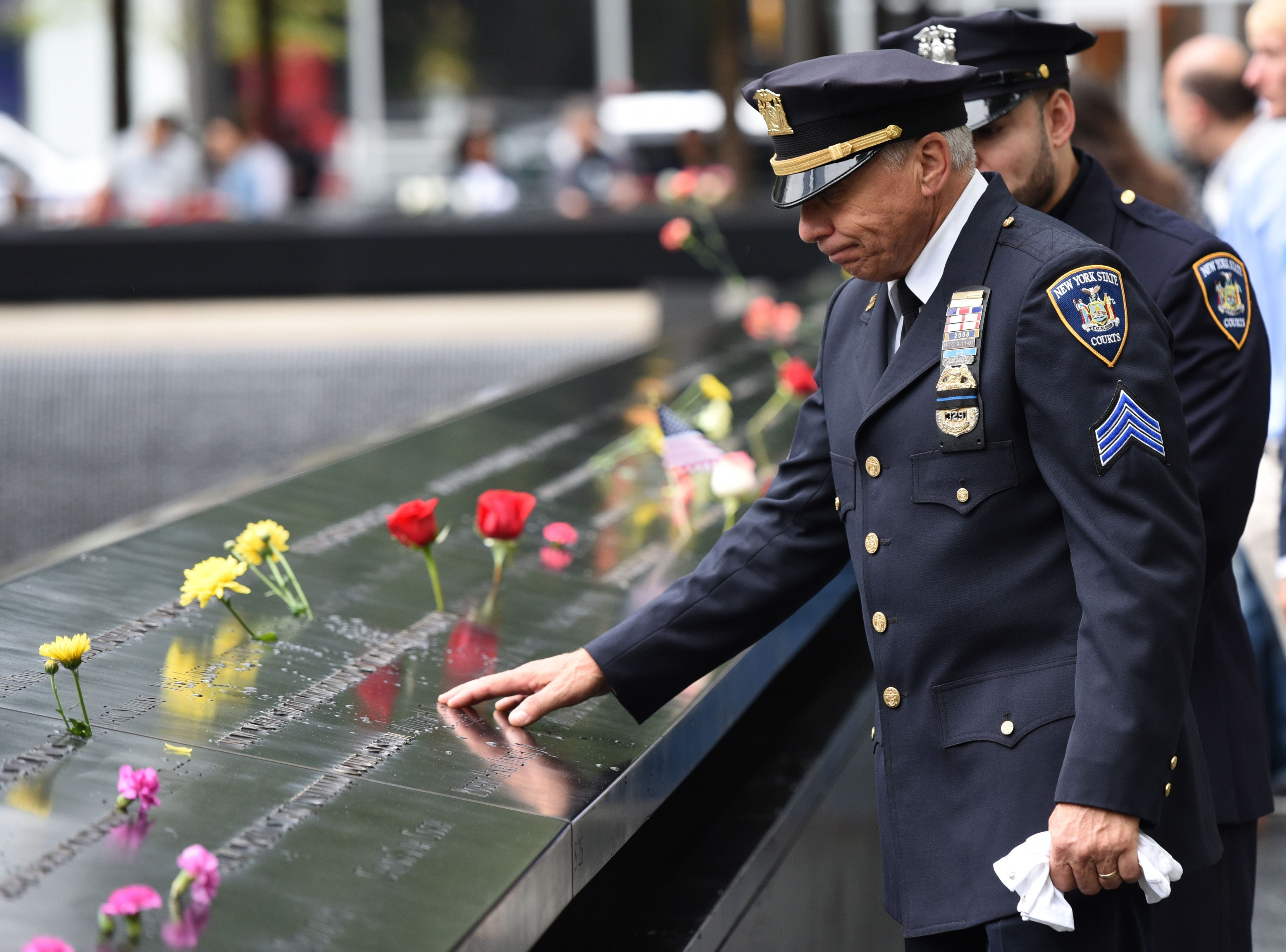 A New York State Court Sergeant looks at names etched into the memorial at the south pool during Sept.11th observances on Sep.11, 2018 in New York.
