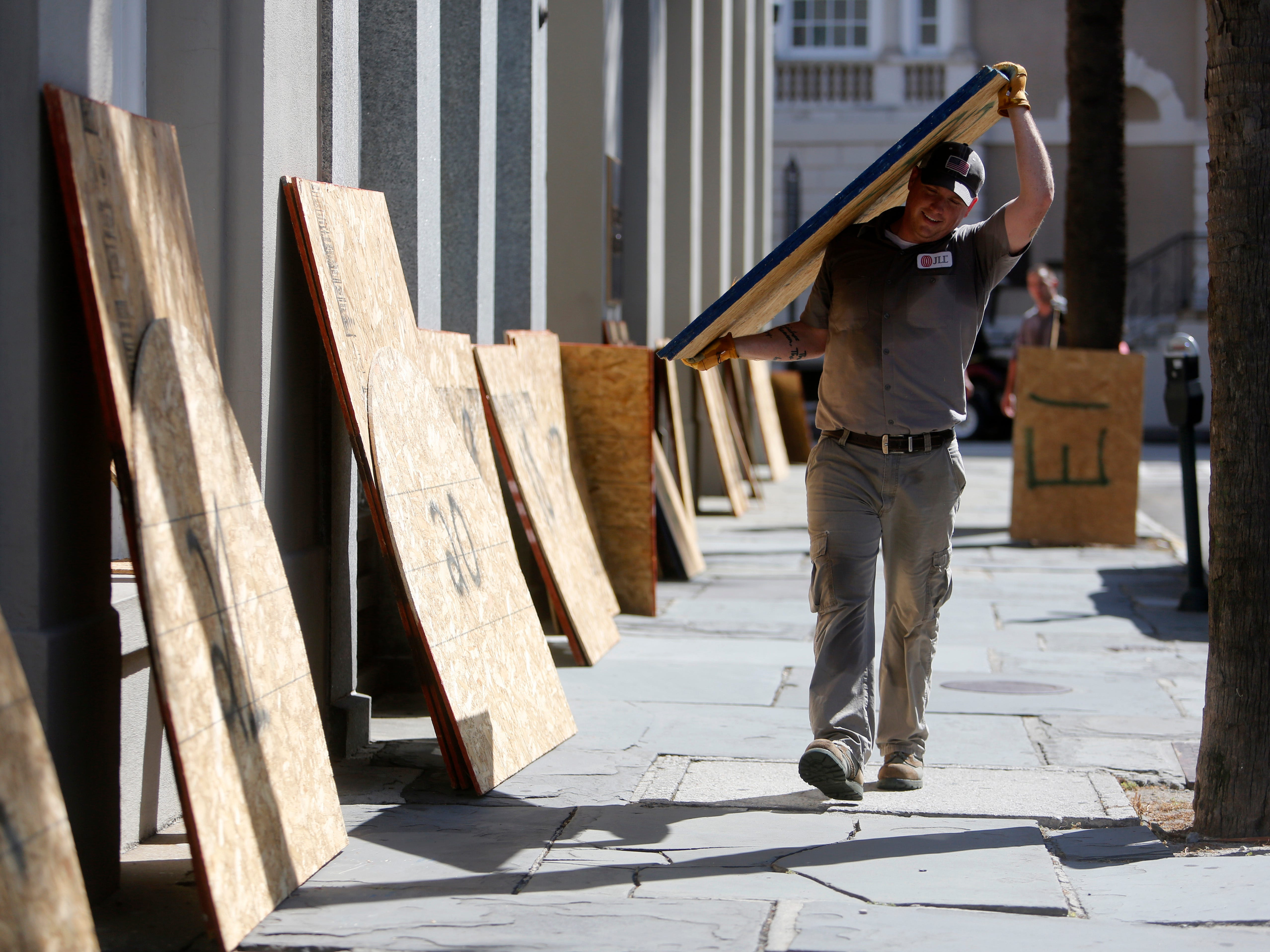 CORRECTS DATE  - Preston Guiher carries a sheet of plywood as he prepares to board up a Wells Fargo bank in preparation for Hurricane Florence in downtown Charleston, S.C., Tuesday, Sept. 11, 2018. (AP Photo/Mic Smith) ORG XMIT: SCMS101