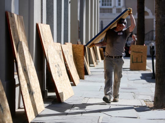 Preston Guiher carries a sheet of plywood as he prepares to board up a Wells Fargo bank in preparation for Hurricane Florence in downtown Charleston, S.C., Tuesday, Sept. 11, 2018. (AP Photo/Mic Smith) ORG XMIT: SCMS101