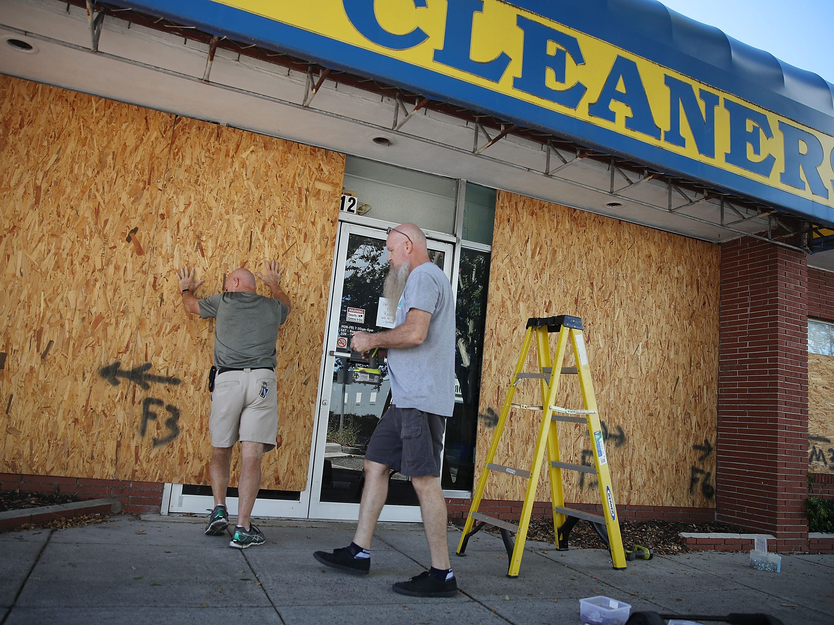 MYRTLE BEACH, SC - SEPTEMBER 11:  Michael Schwartz (L) and Jay Schwartz secure plywood over the windows of their business ahead of the arrival of Hurricane Florence on September 11, 2018 in Myrtle Beach, South Carolina. Florence is expected to make landfall by late Thursday to near Category 5 strength along the Virginia, North Carolina and South Carolina coastline.  (Photo by Joe Raedle/Getty Images) ORG XMIT: 775225768 ORIG FILE ID: 1031243328