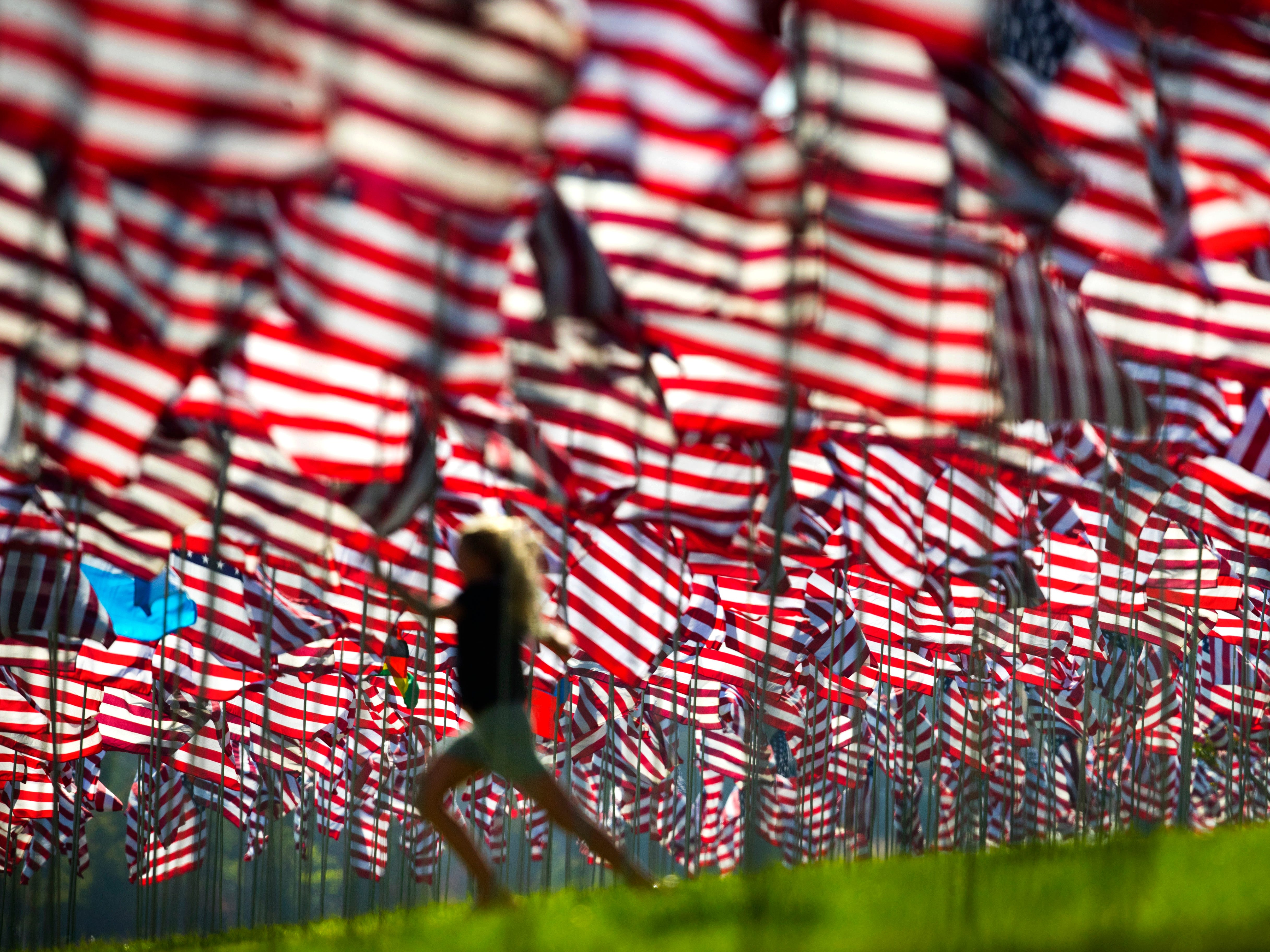 Callie Cirulnick, 10, visits the Pepperdine University's annual display of flags honoring the victims of the 9/11 terrorist attacks, Monday, Sept. 10, 2018, in Malibu, Calif. Terrorists used hijacked planes to crash Sept. 11, 2001, into the World Trade Centers, the Pentagon and a field in Pennsylvania. Nearly 3,000 people were killed in the attacks. (AP Photo/Jae C. Hong) ORG XMIT: CAJH102
